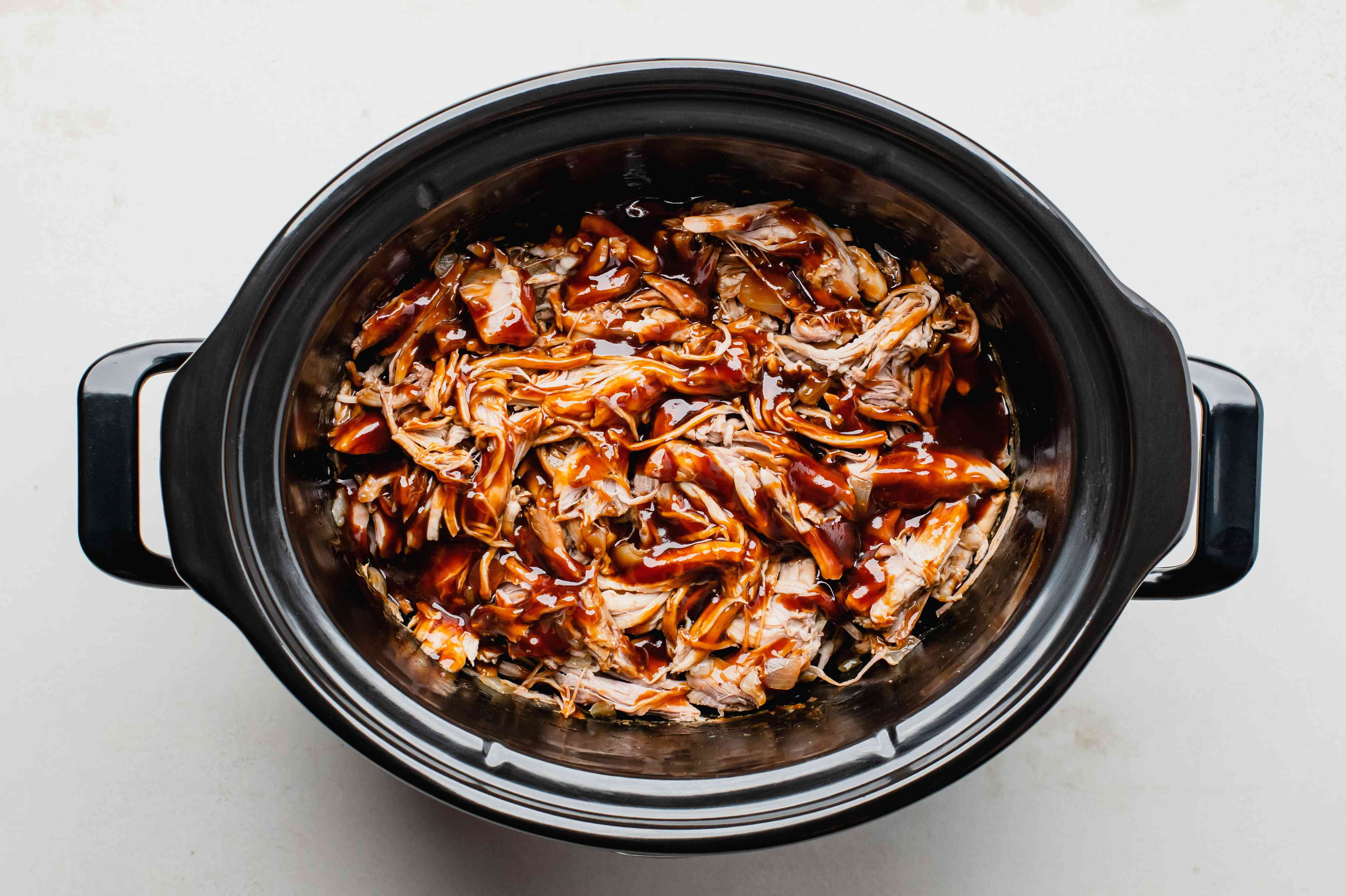 Barbecue sauce added to shredded pork in cooker