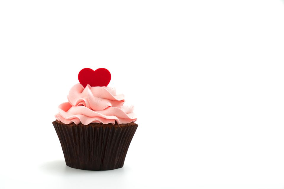 Cupcake with pink frosting and a red candy heart on top