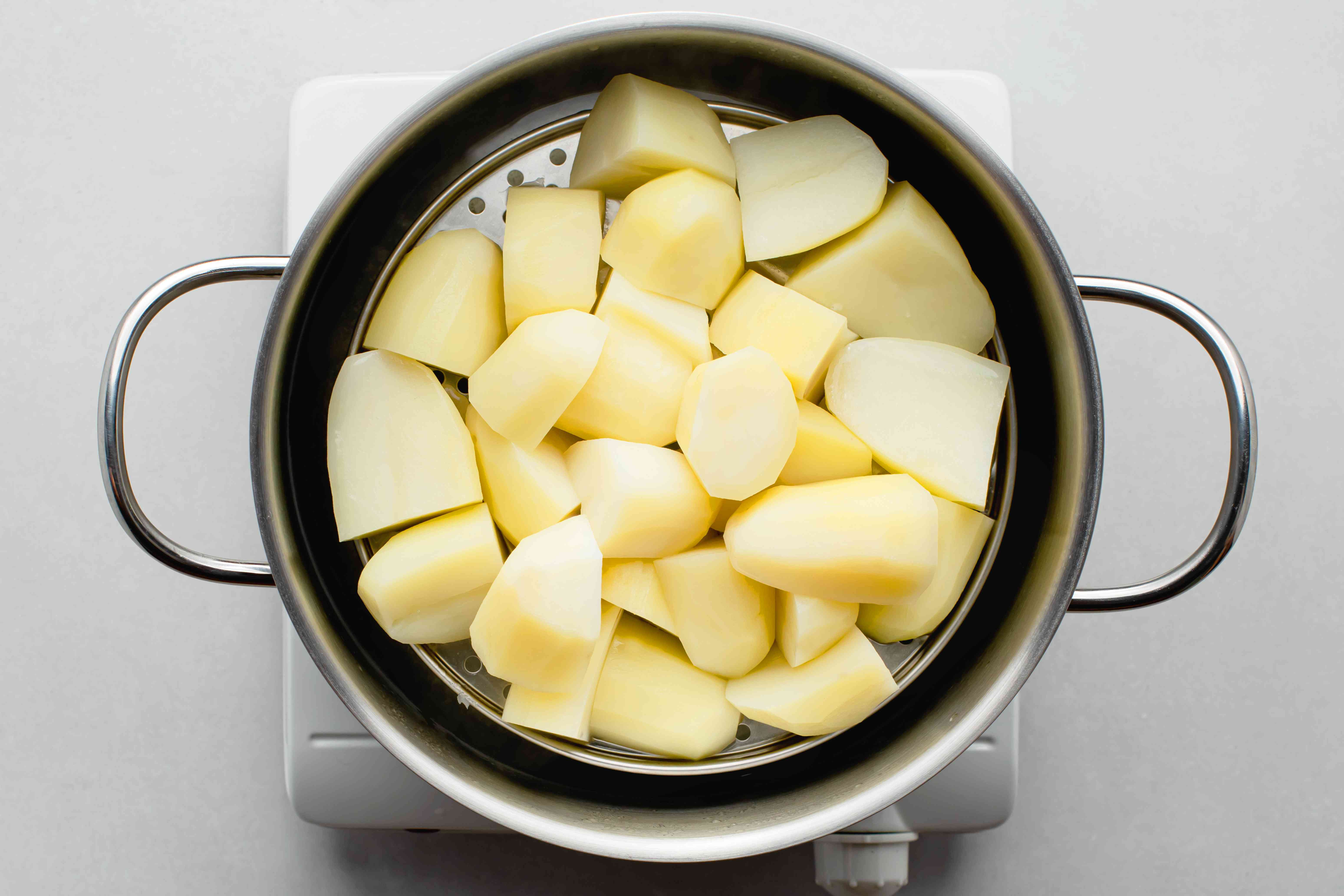 Potatoes steaming in a pot with a steamer insert