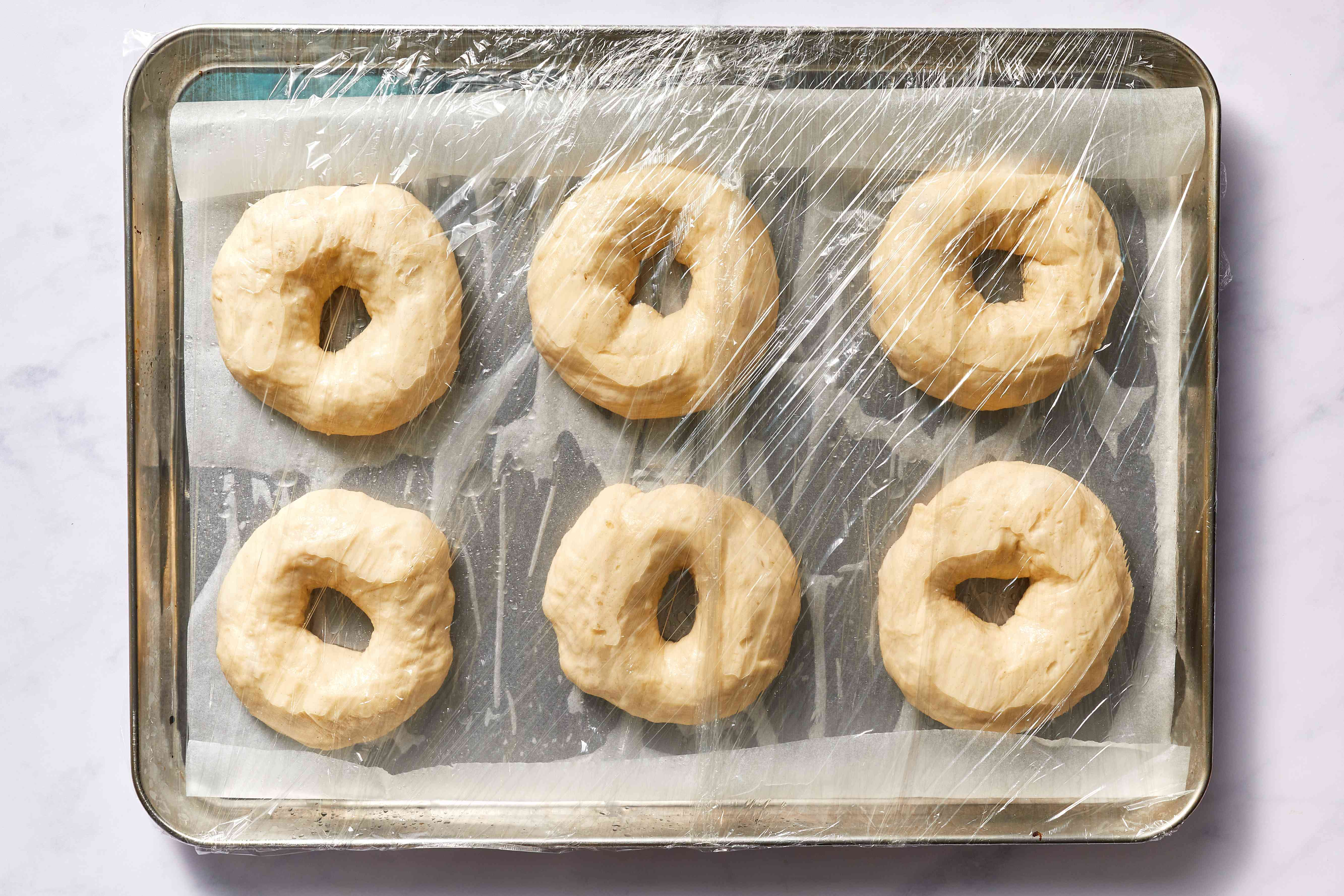bagel dough on a parchment paper lined baking sheet, covered with plastic wrap