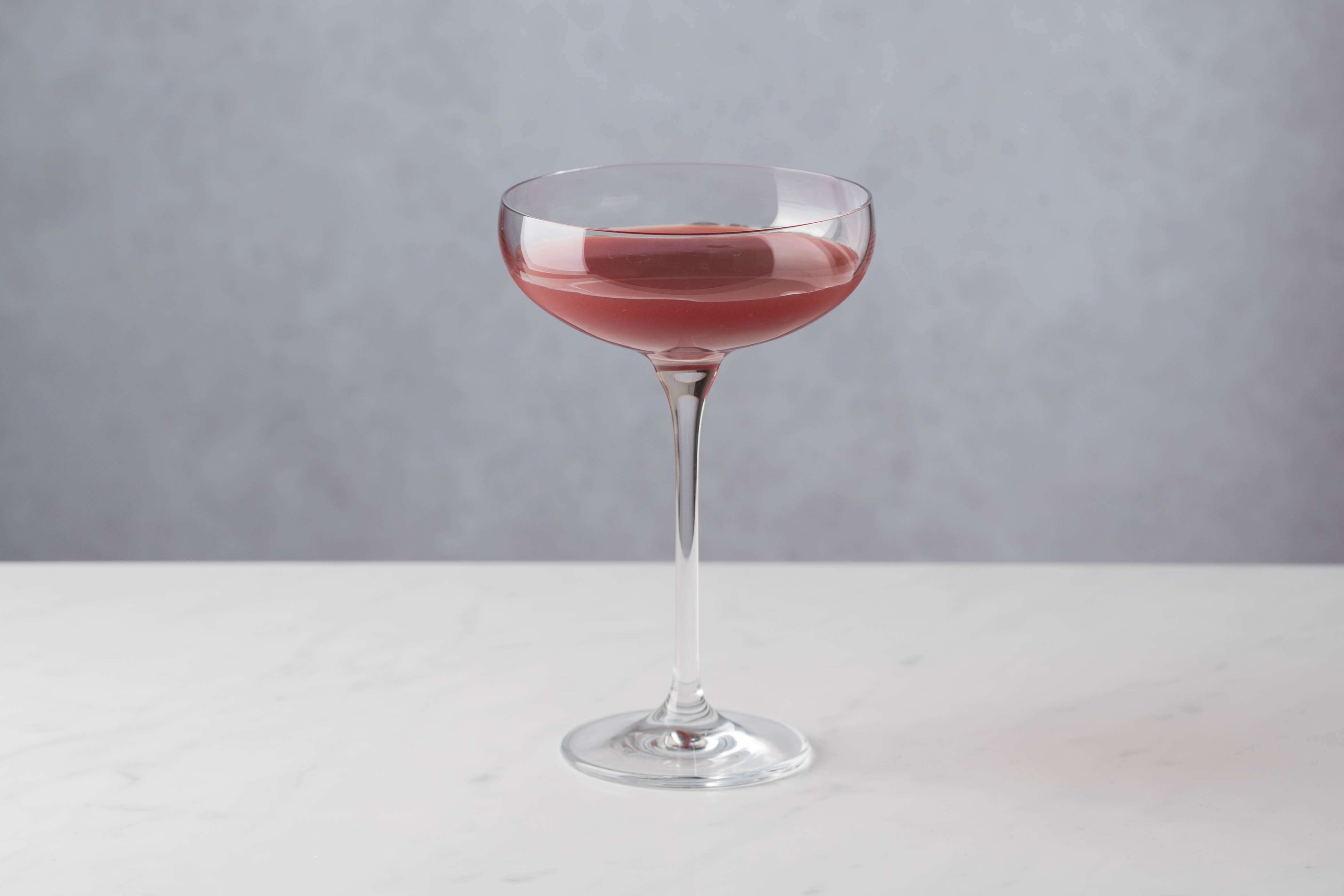 Strain the cocktail into a Champagne flute