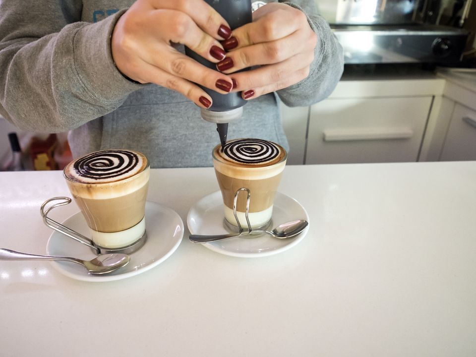 Waitress preparing a coffee with milk condesada and adornments of chocolate on the foam, on the countertop of a bar