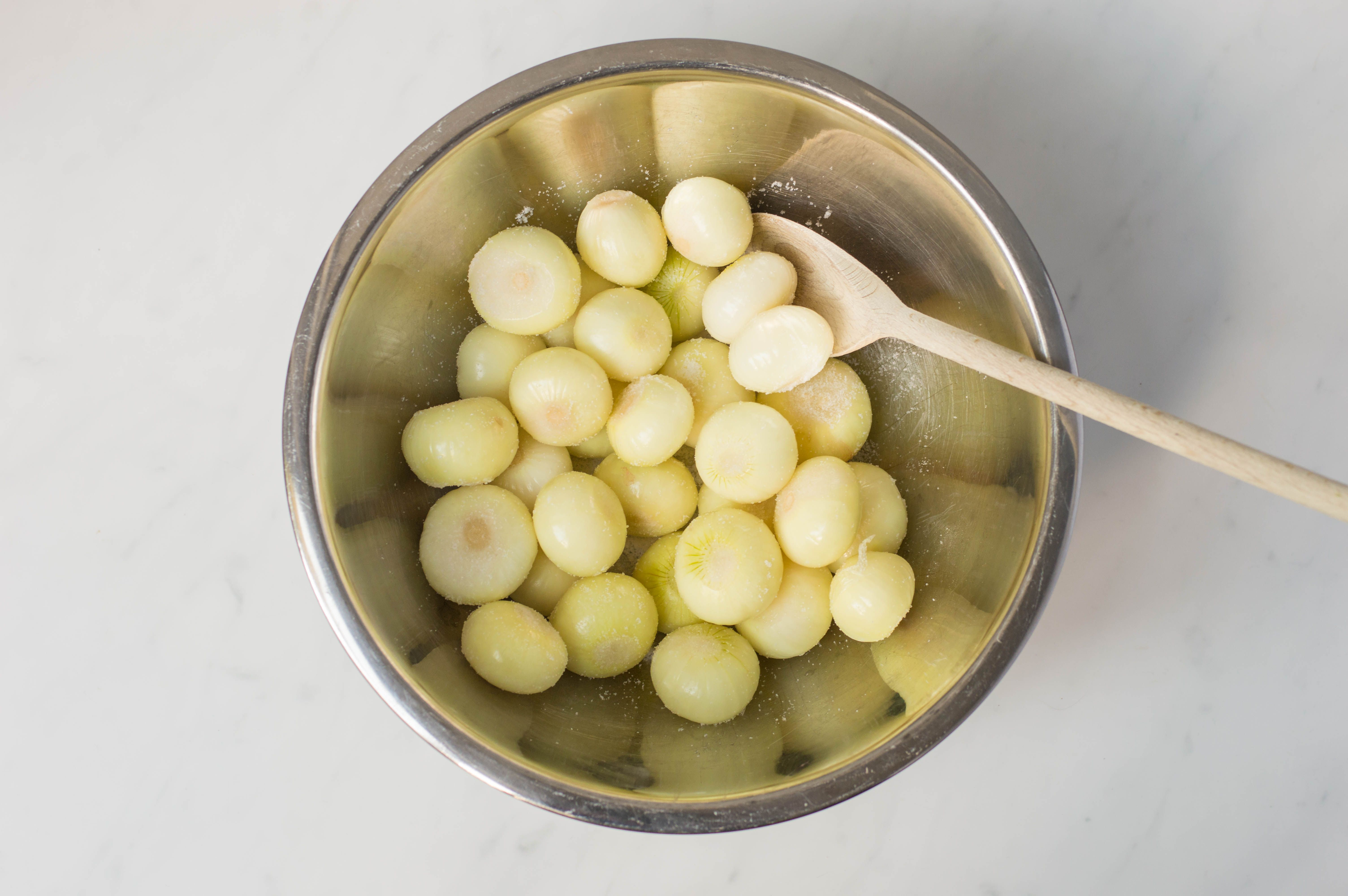 Salted button onions in bowl, stirred