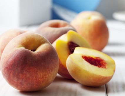 Whole and sliced peaches (Prunus persica) on white wooden table