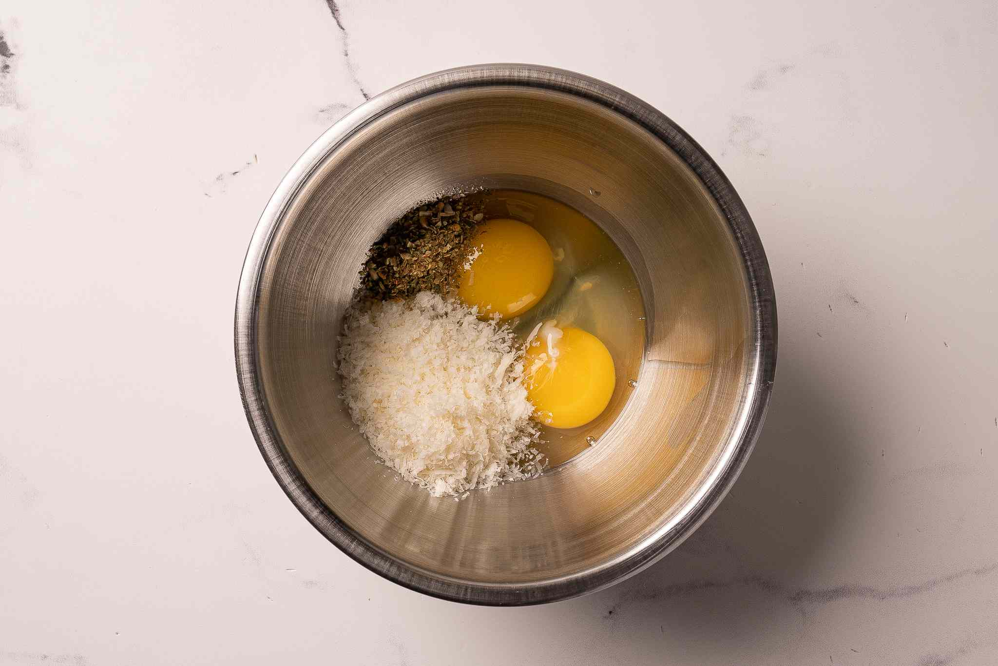 Eggs, parmesan, and seasoning in a bowl