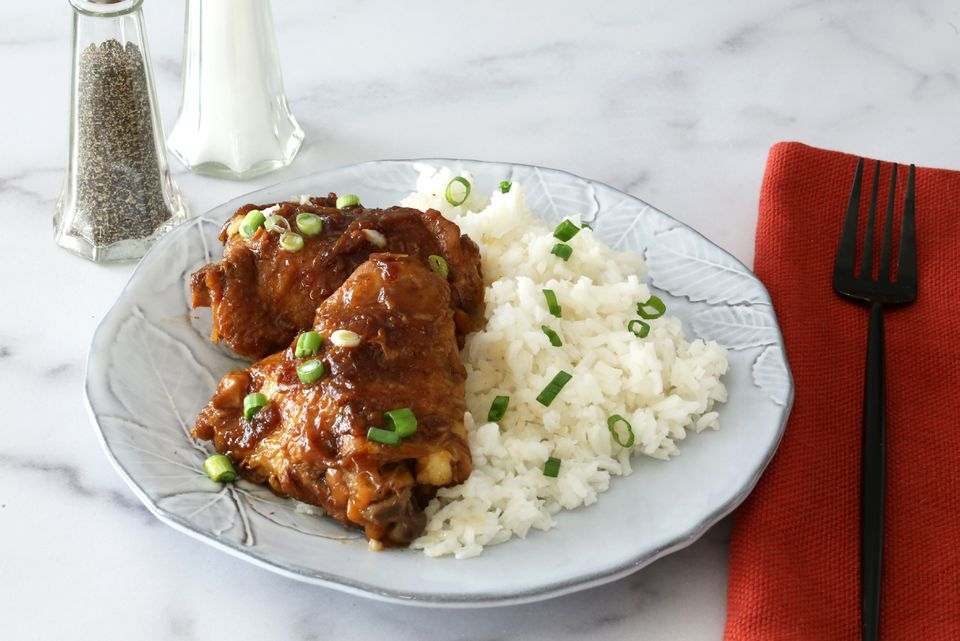Instant Pot chicken adobo on a plate with rice.