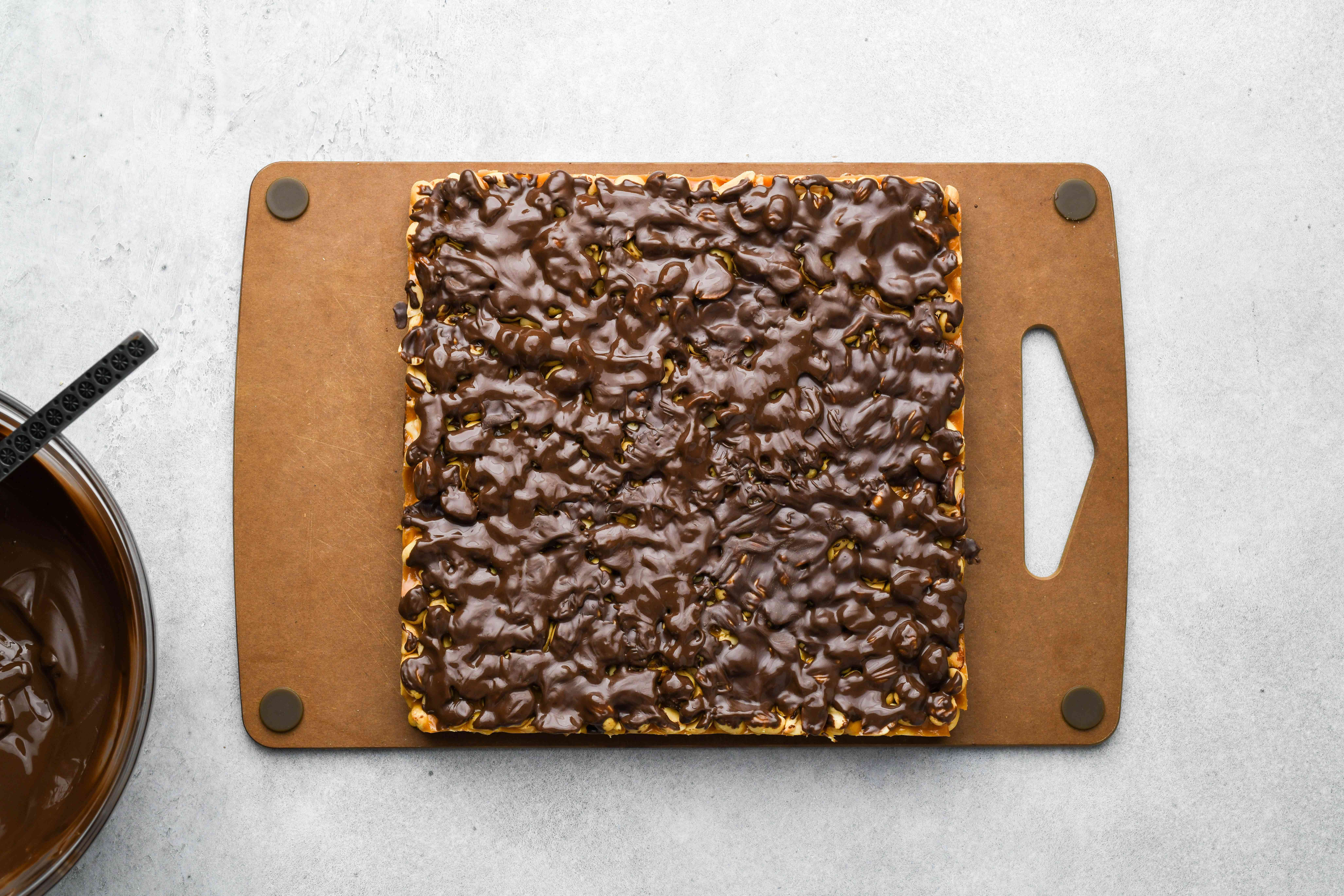 chocolate covered peanut and caramel on a cutting board