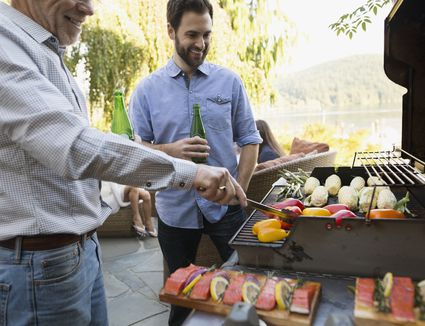Father and son drinking beer barbecuing on patio
