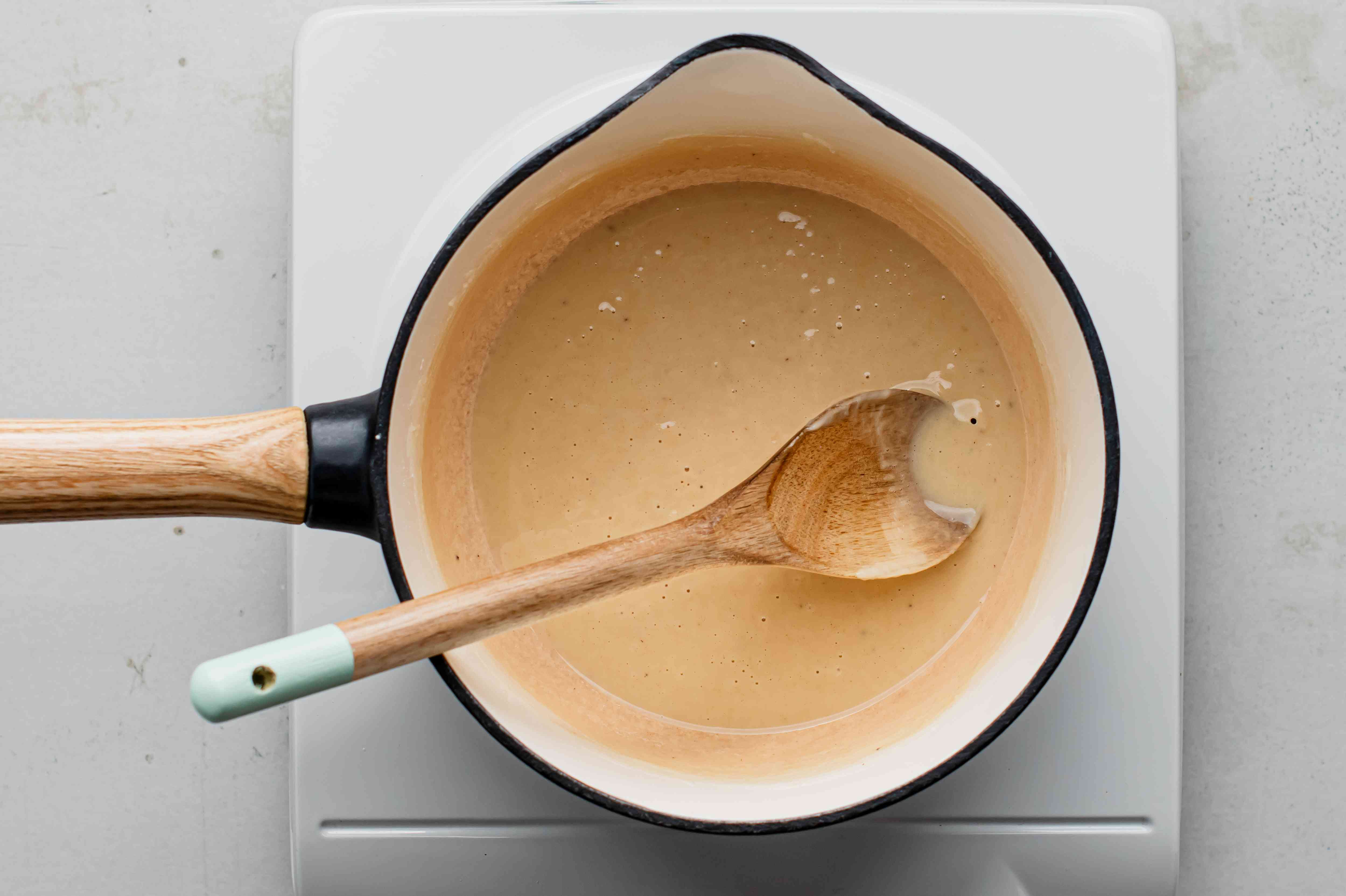Light brown roux in a saucepan with a wooden spoon
