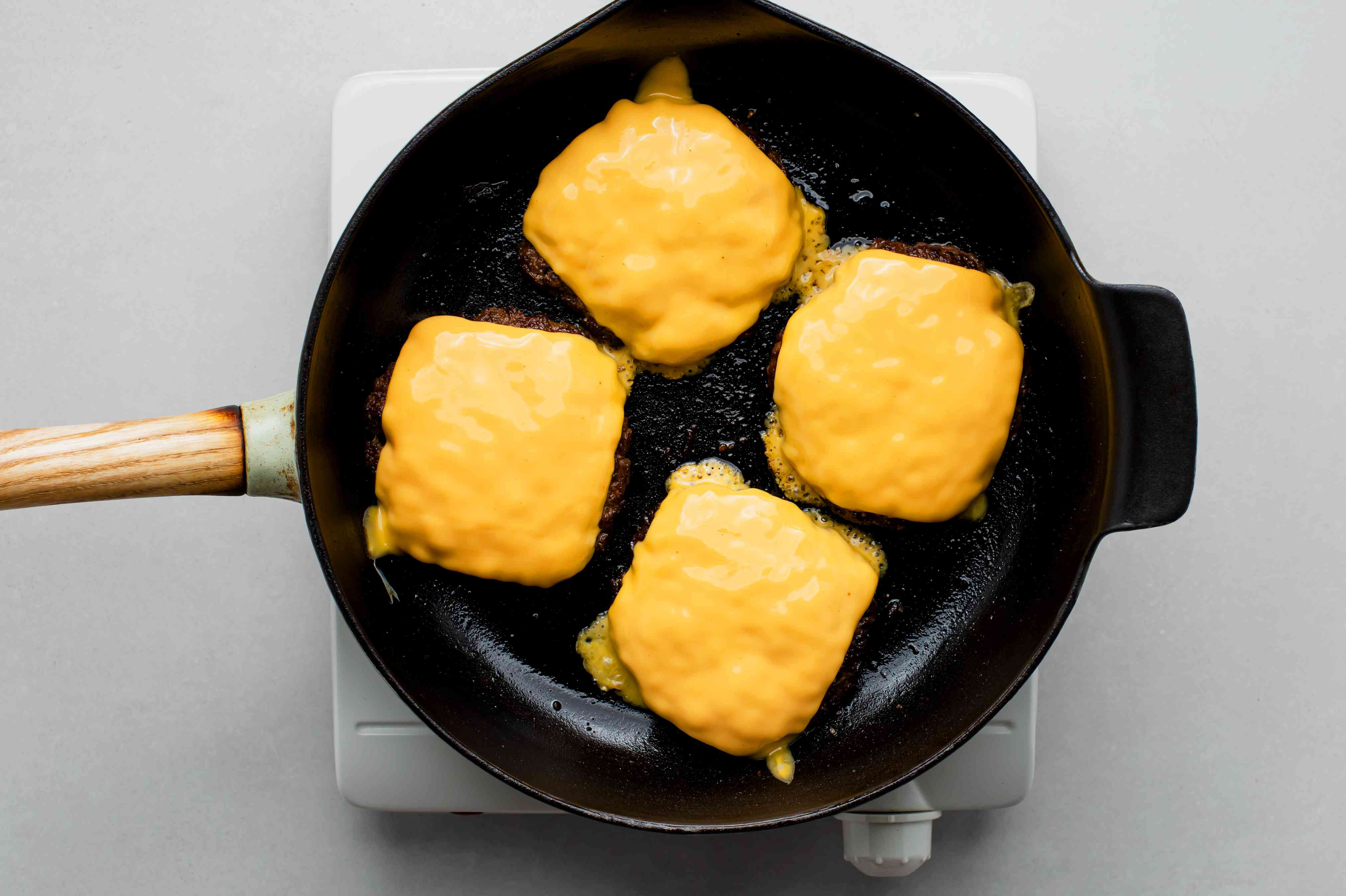 beef patties with cheese in a frying pan