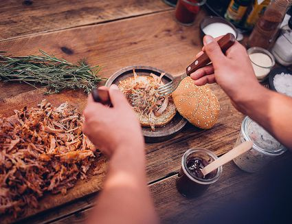 Person making pulled pork sandwich