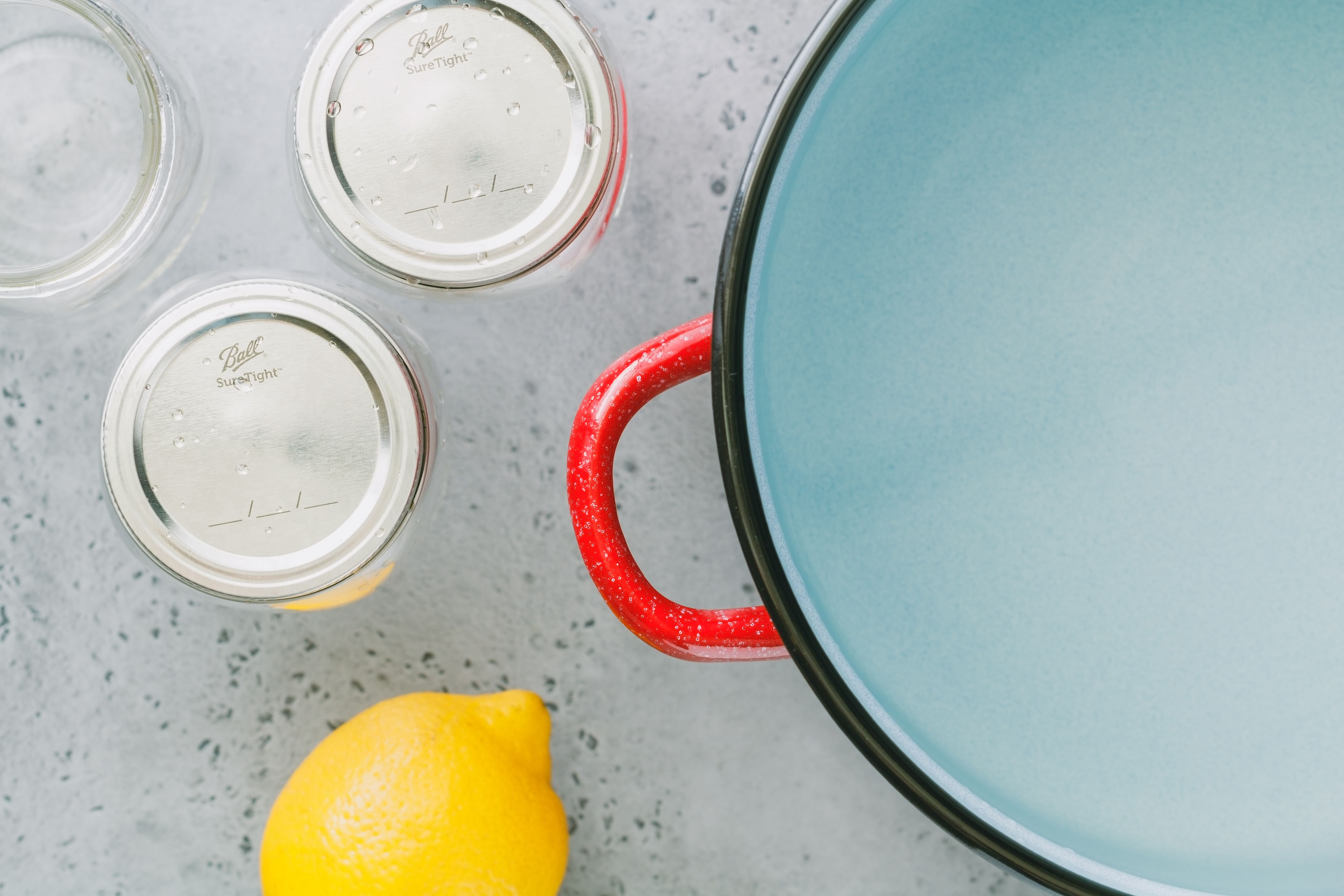 Jars with lids next to a dutch oven filled with water