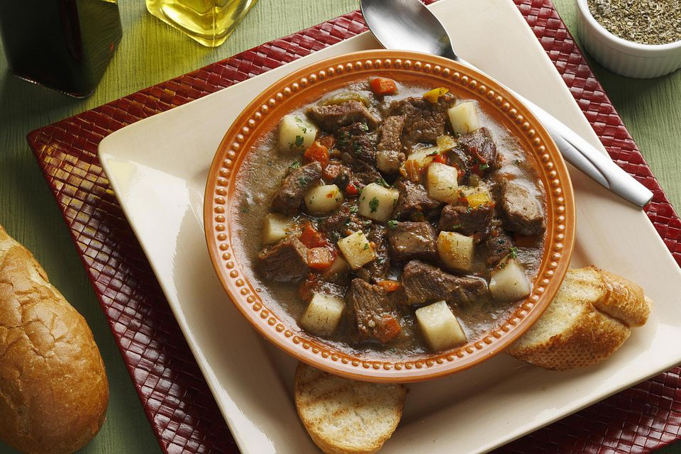 beef stew on a plate with bread on the side