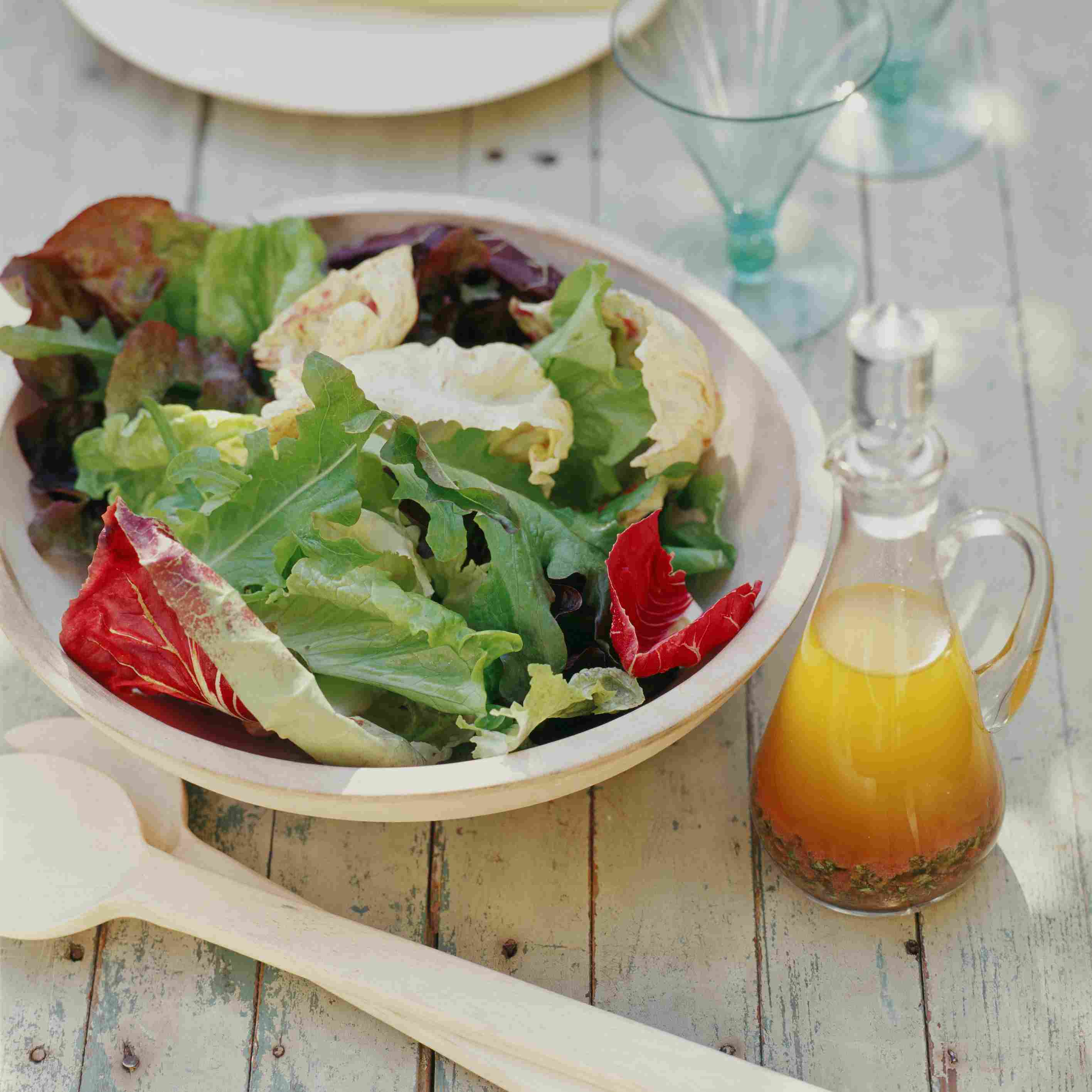 Salad in a wooden bowl with vinaigrette.