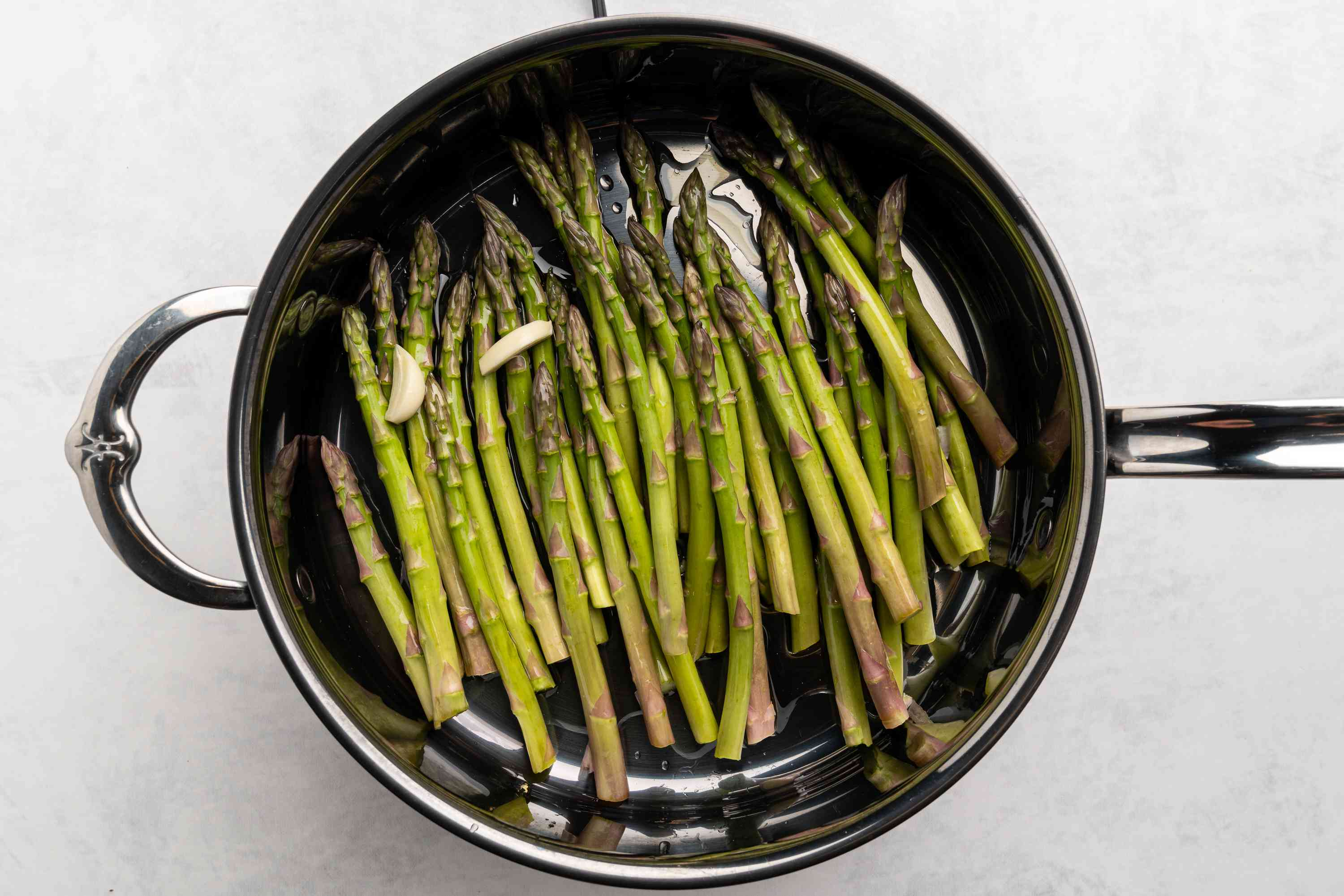 asparagus, olive oil, water, and garlic to a large sauté pan