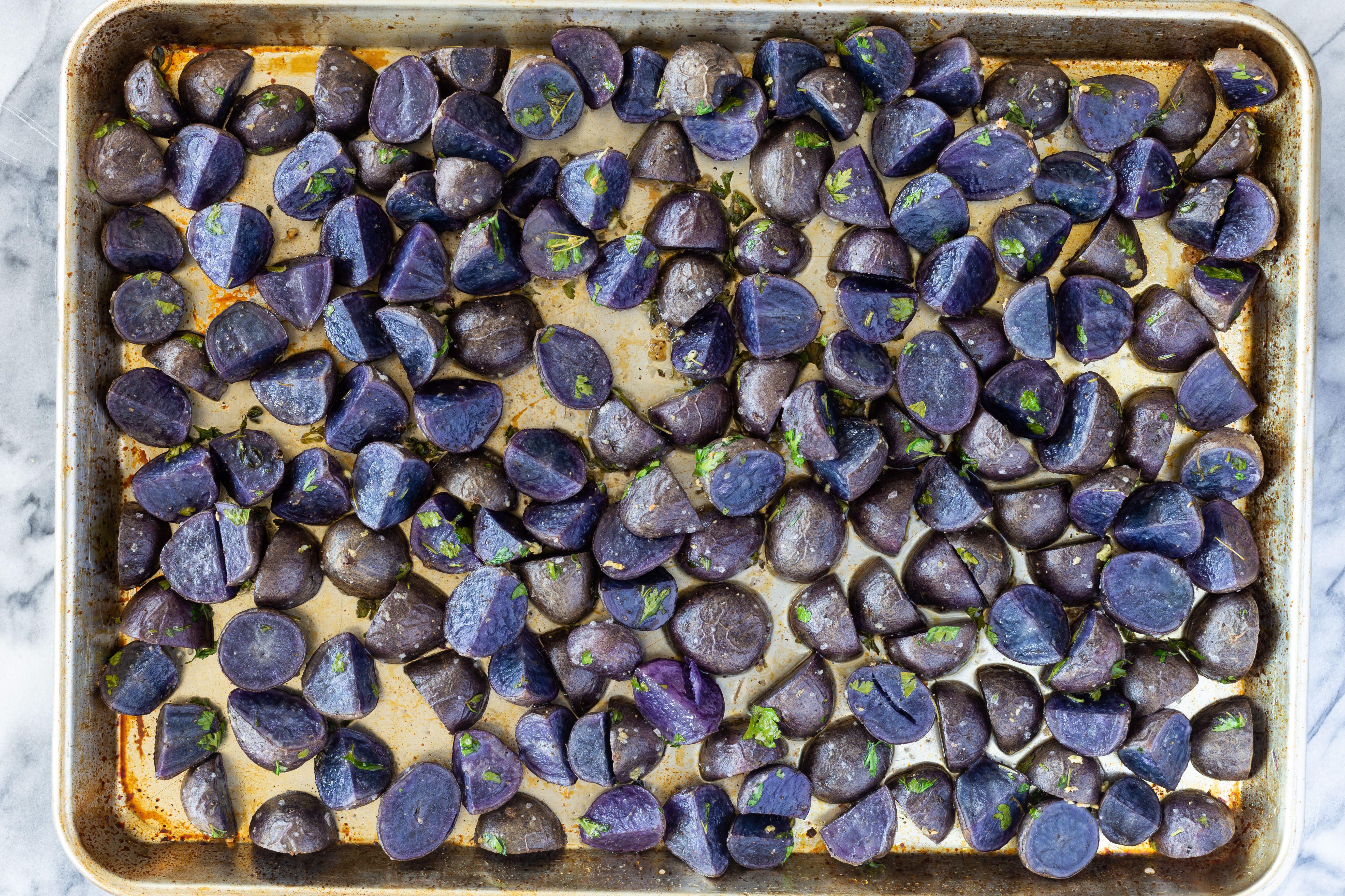 Roasted purple potatoes on baking pan