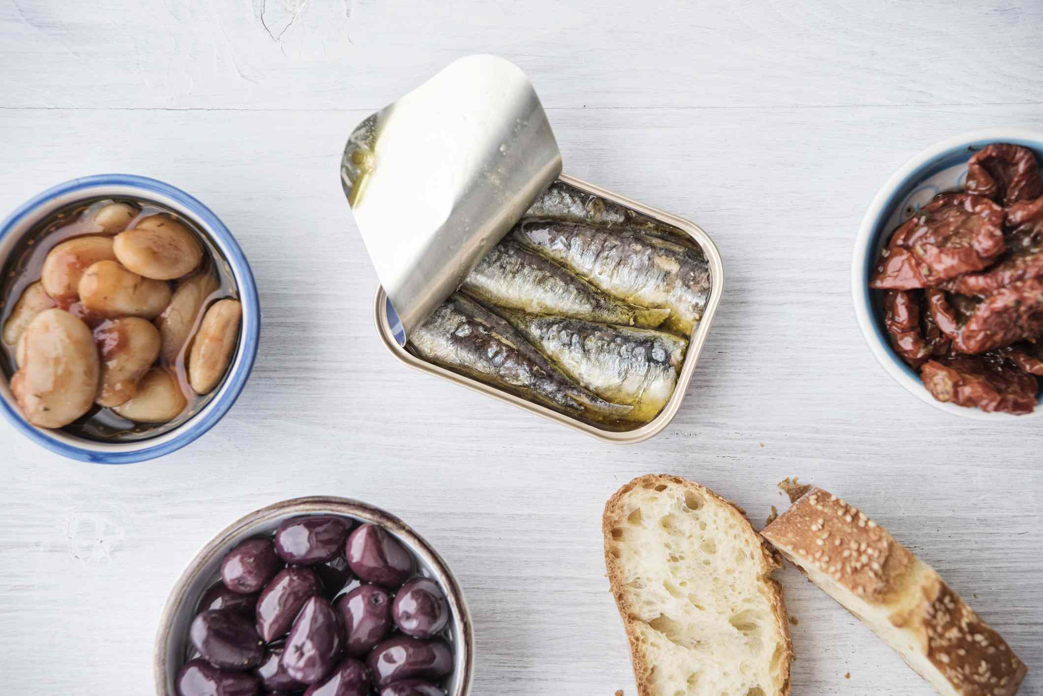 variety of canned seafood products and bread on light wooden surface