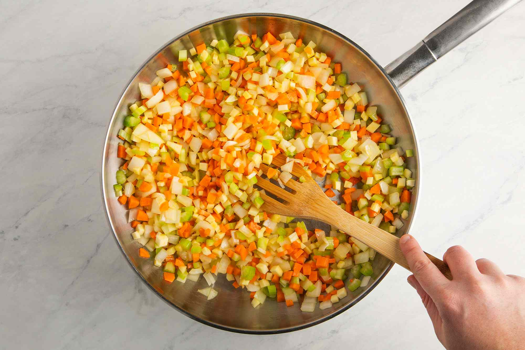 onions, carrots, parsnips, and celery cooking with lard in a skillet