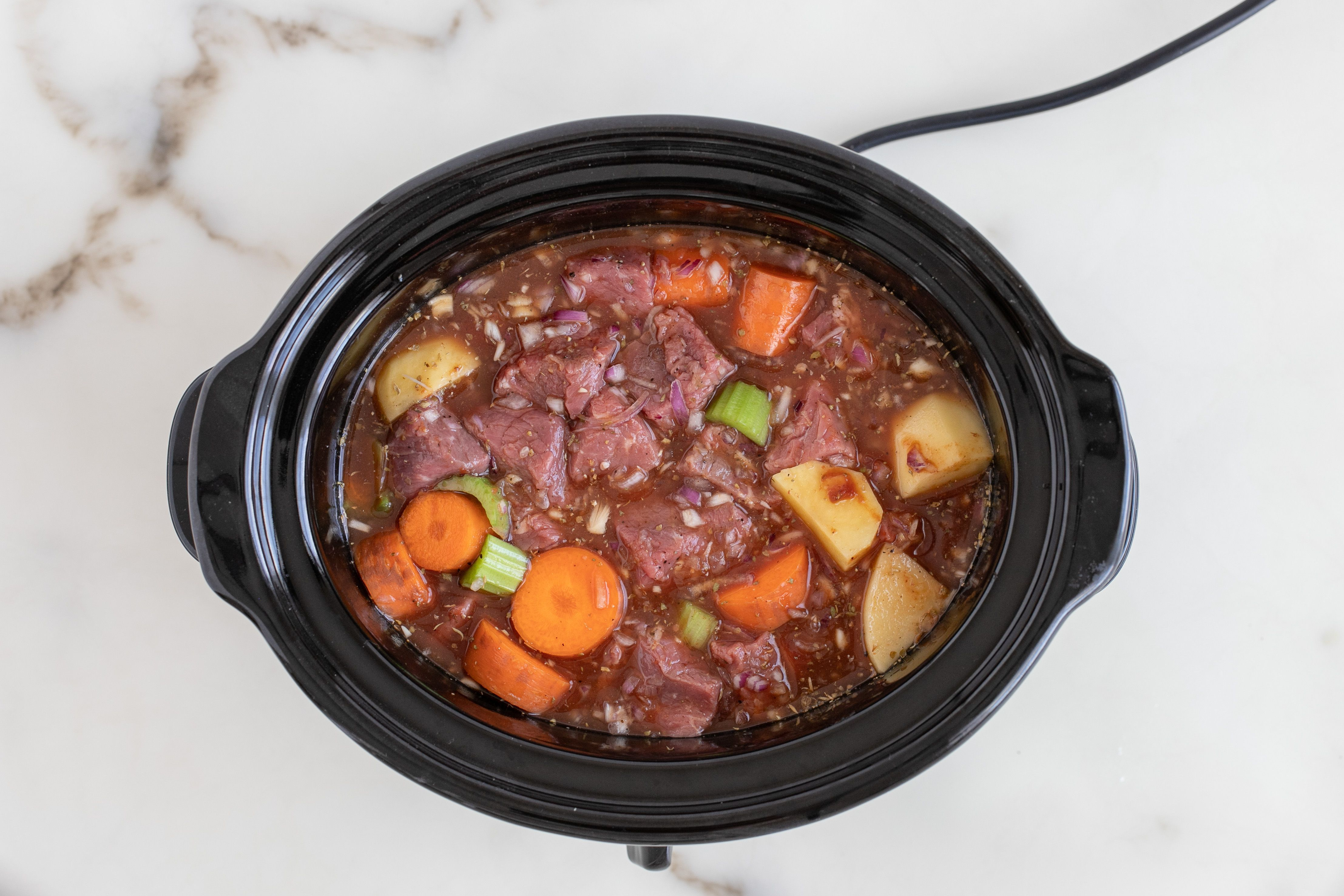 Slow cooker filled with ingredients