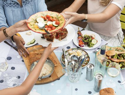 Friends sharing plates of food at dinner party