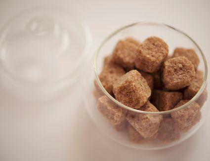 A glass bowl of brown sugar cubes