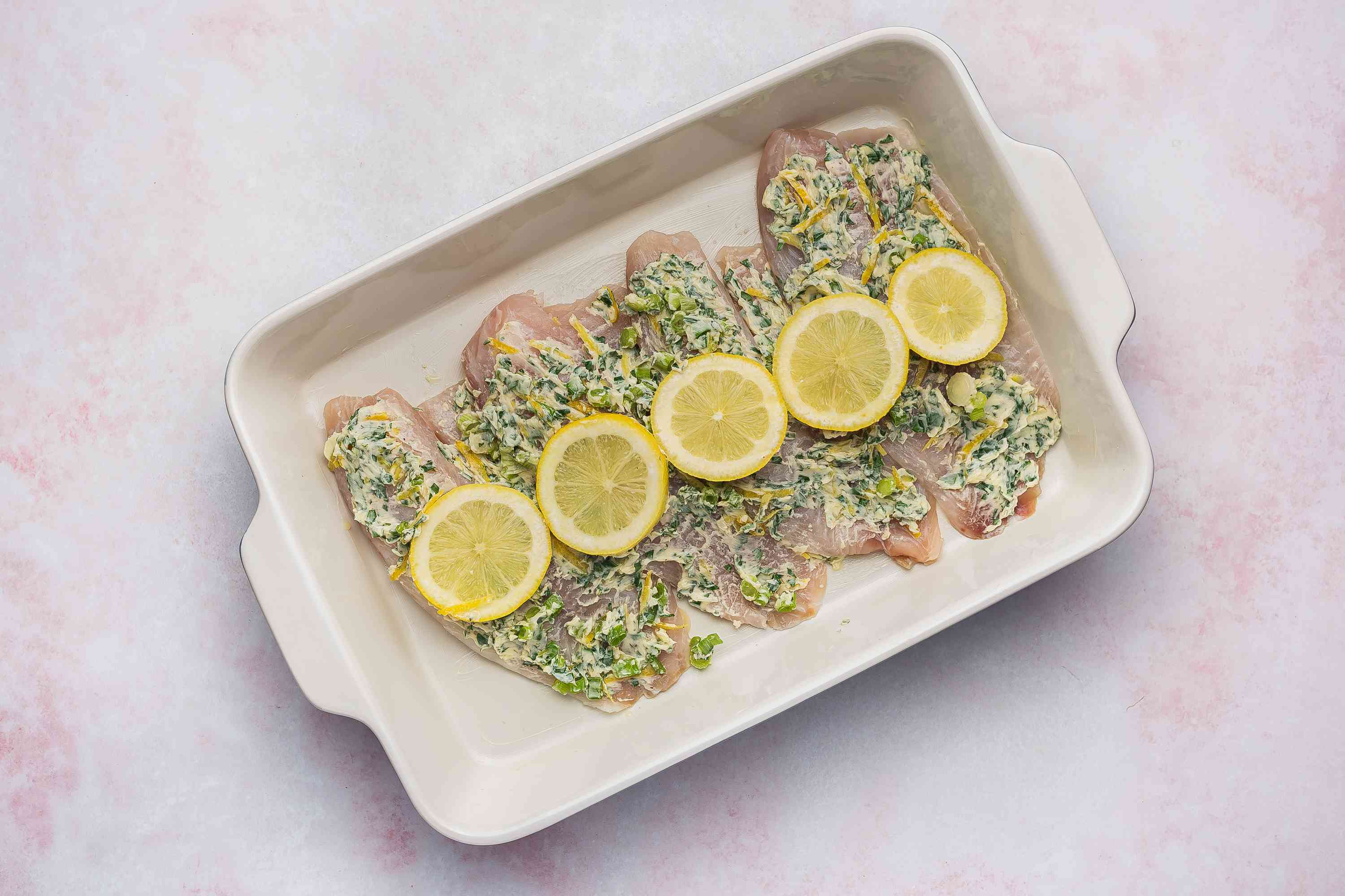 Tilapia, butter mixture, and lemon rounds in a baking dish