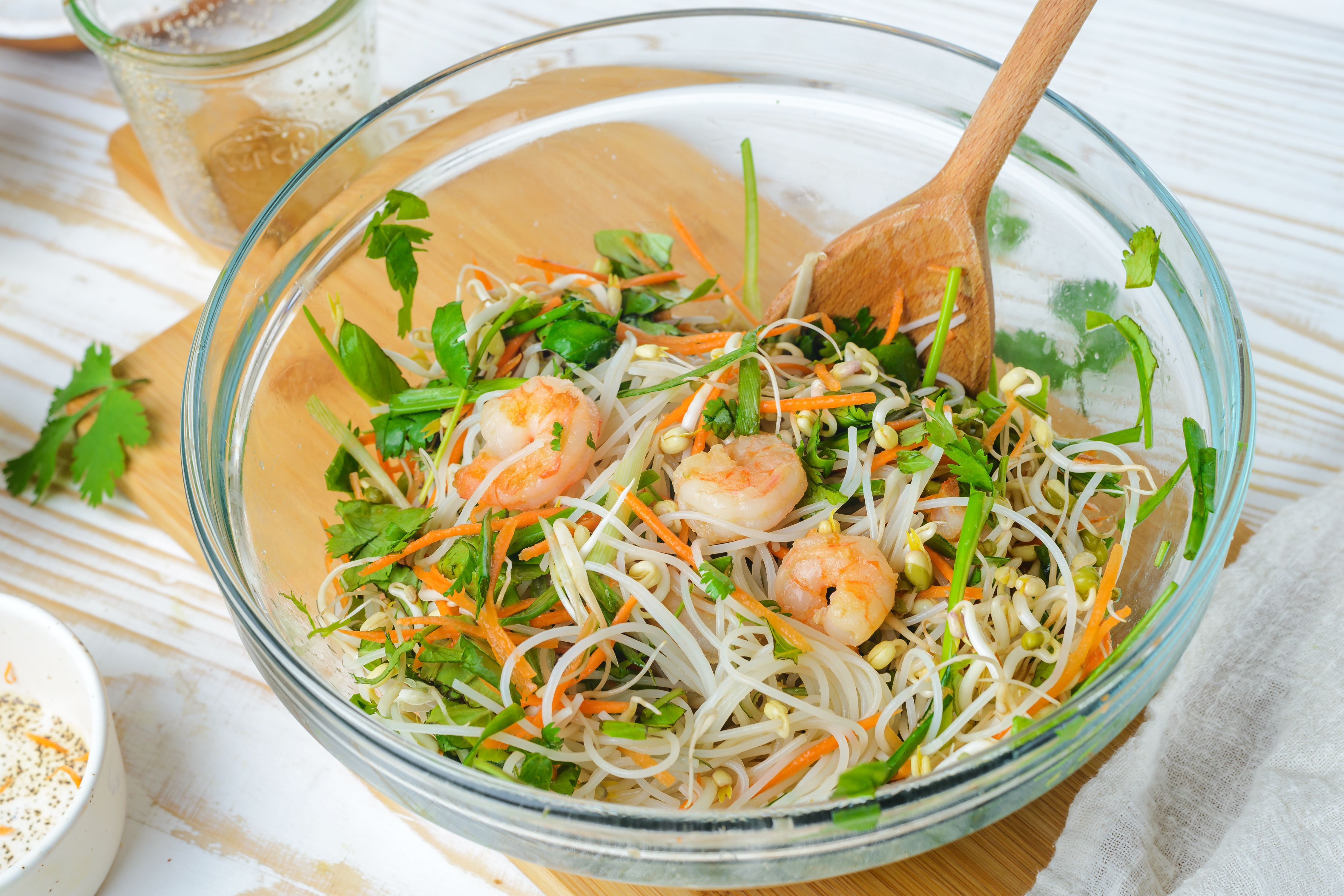Ingredients for Thai spring rolls in a bowl with a wooden spoon