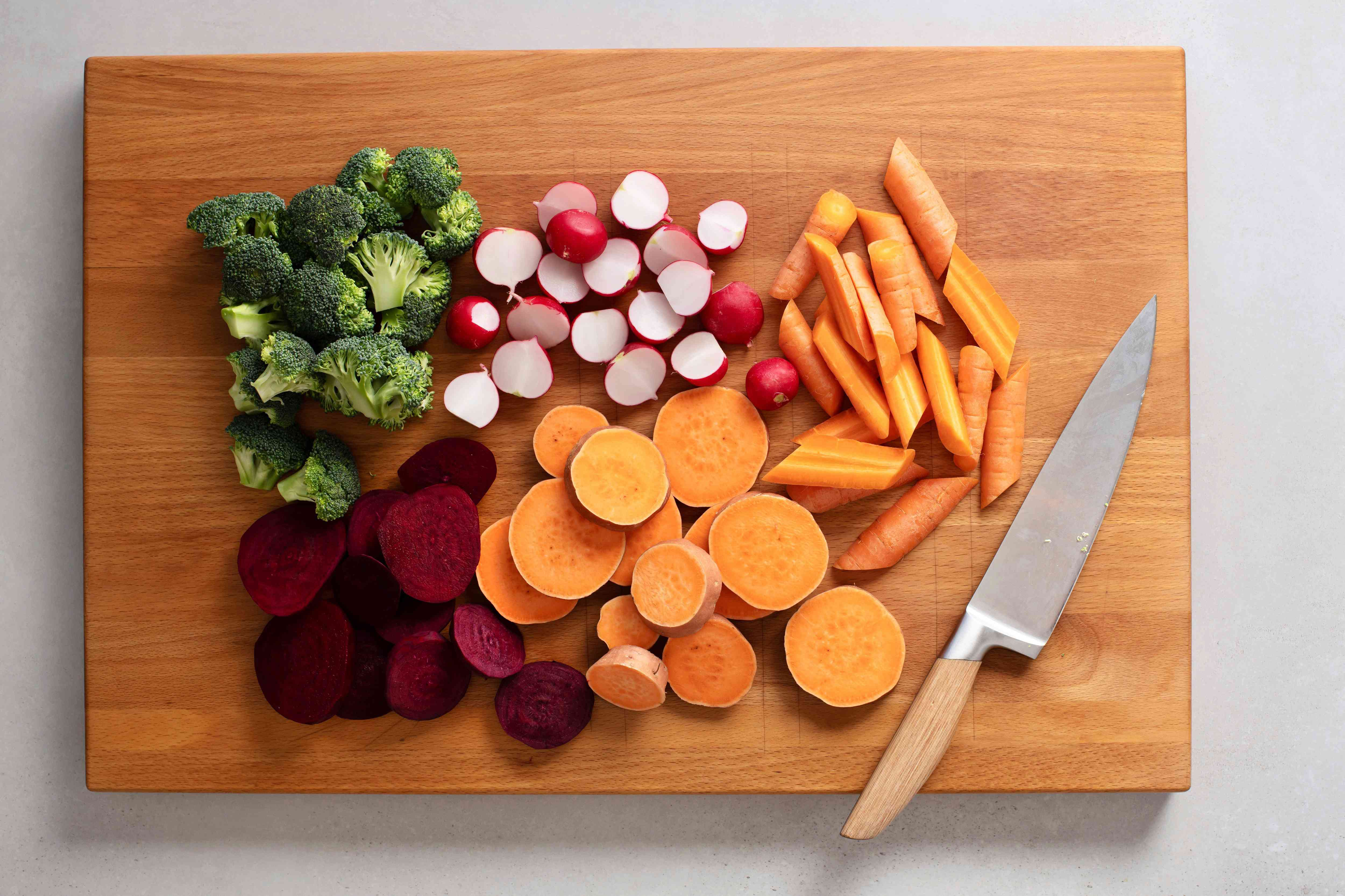 broccoli, radishes, carrots, beets, and yams cut on cutting board with a knife