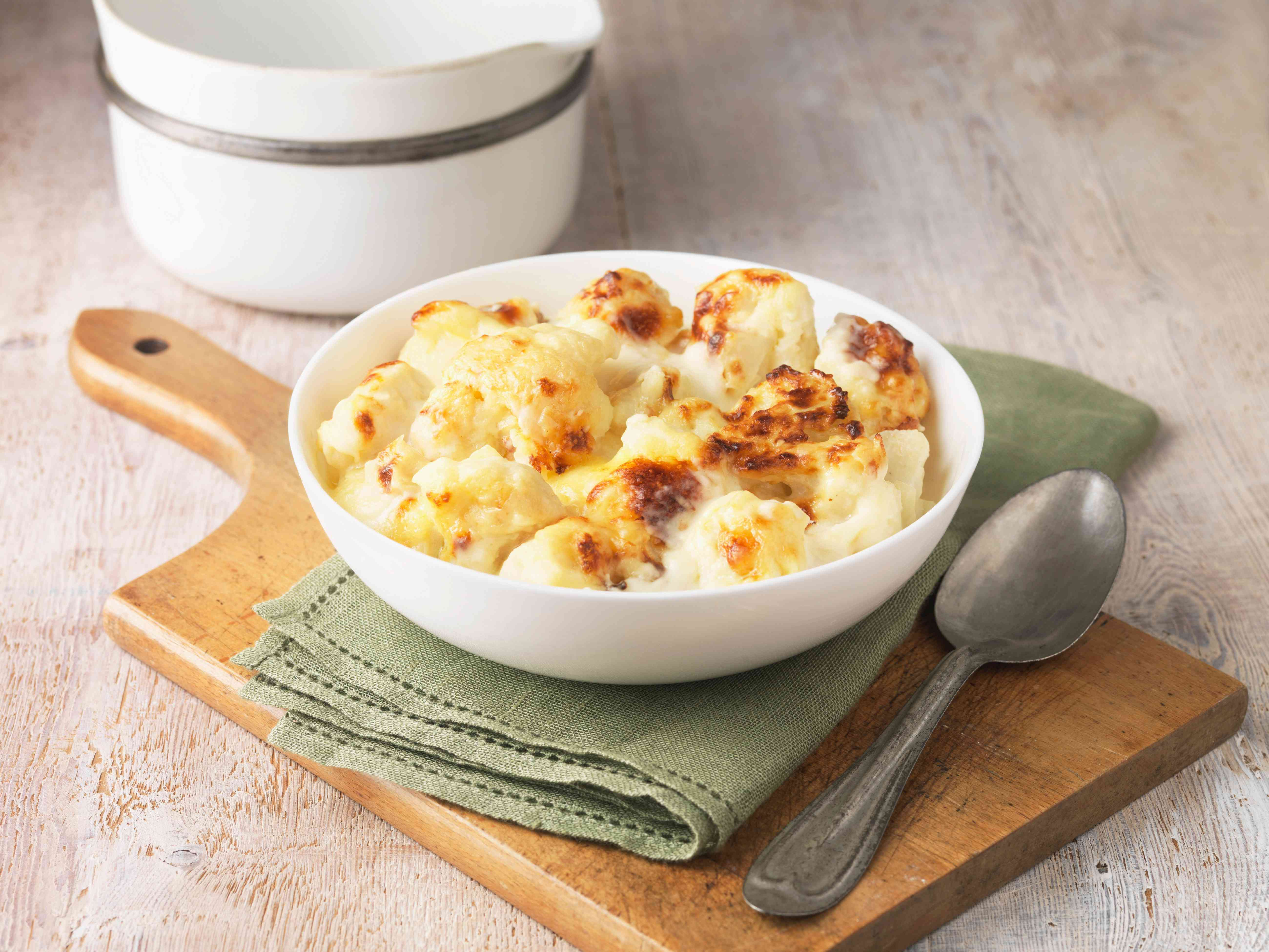 Cauliflower cheese in white bowl with green napkin and spoon