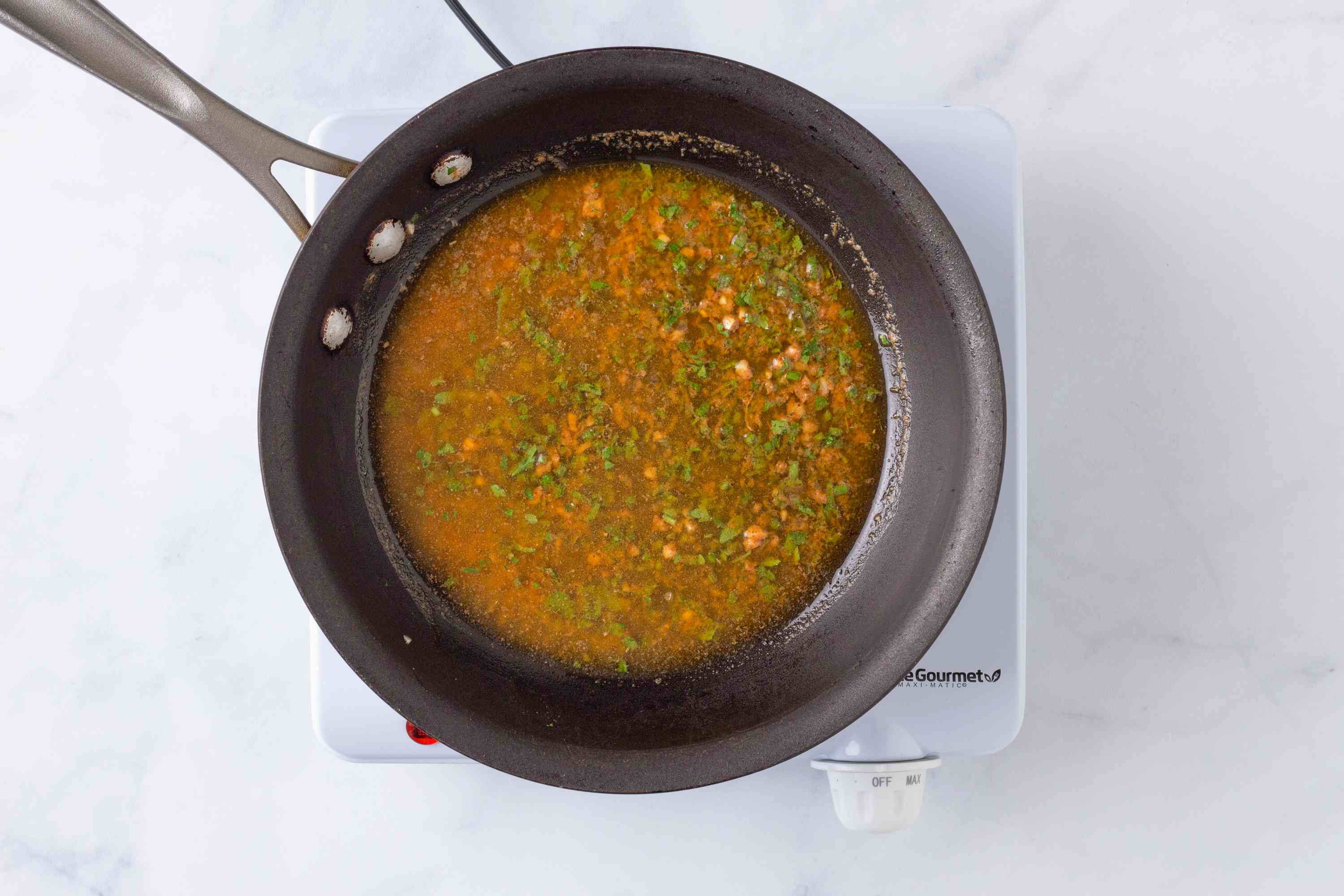 Butter, spices, and herbs melting in a skillet
