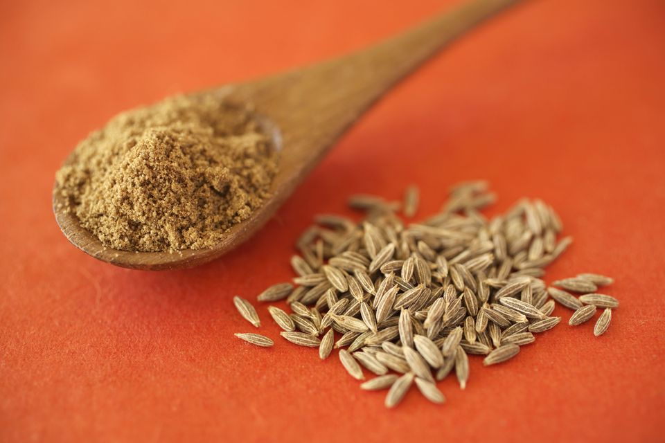 Cumin powder in spoon, cumin seeds on table