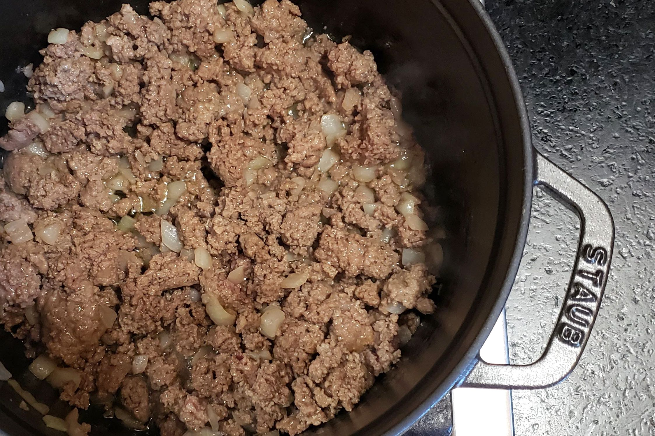 Brown the ground beef in a large deep skillet or Dutch oven.