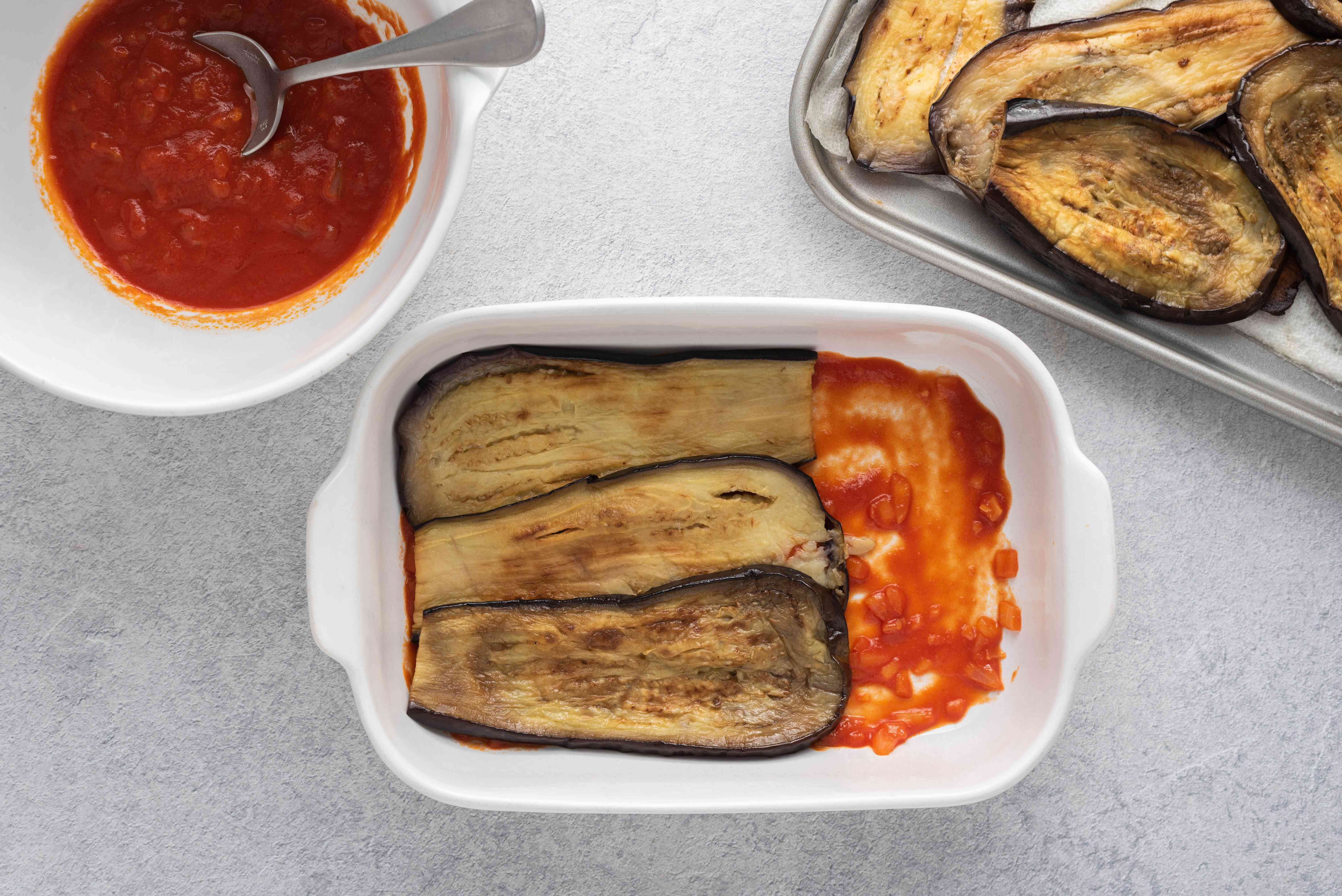eggplant on top of sauce in a baking dish