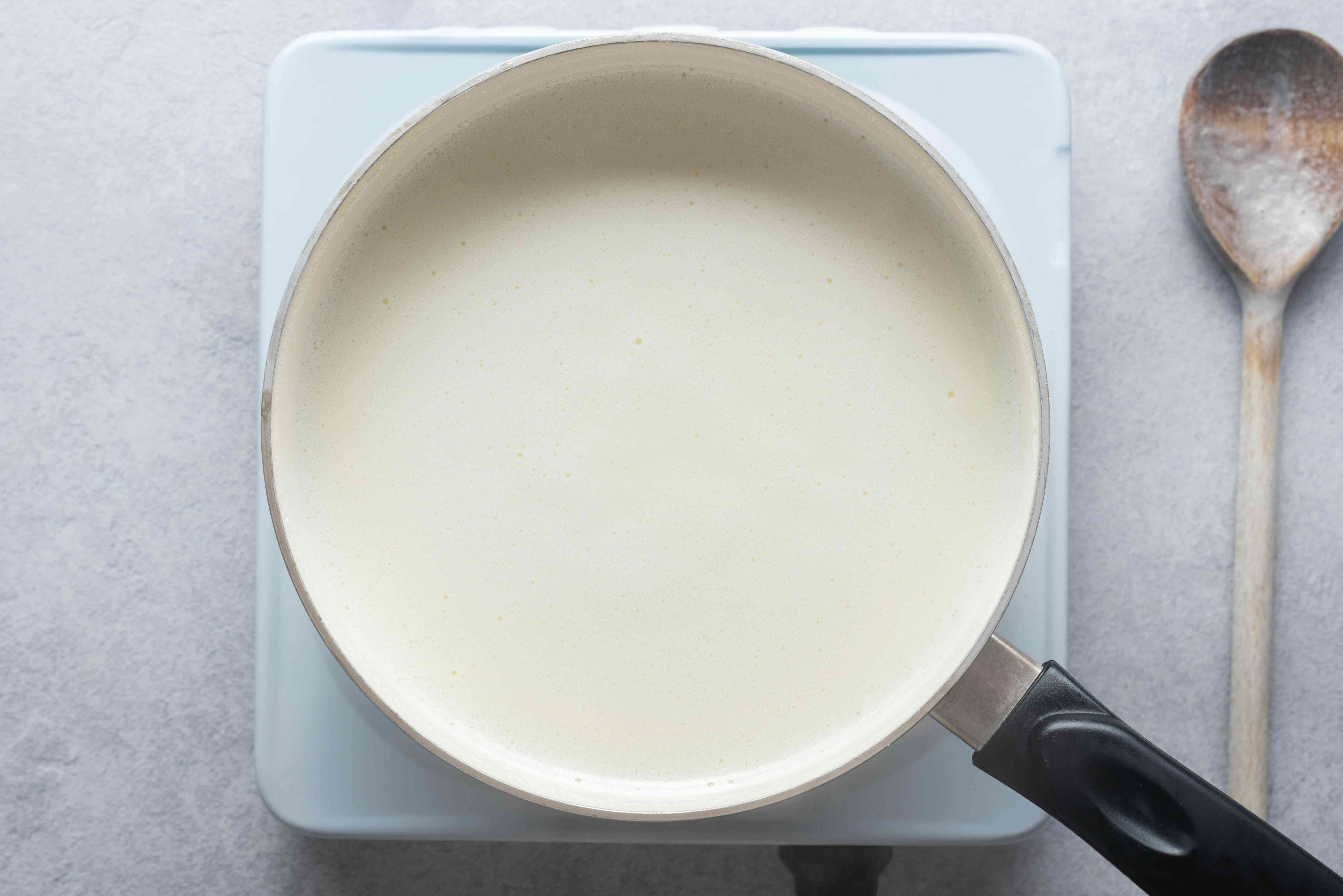 Milk, sugar, and vanilla boiling with rice in a saucepan