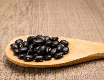 Black beans in wooden spoon