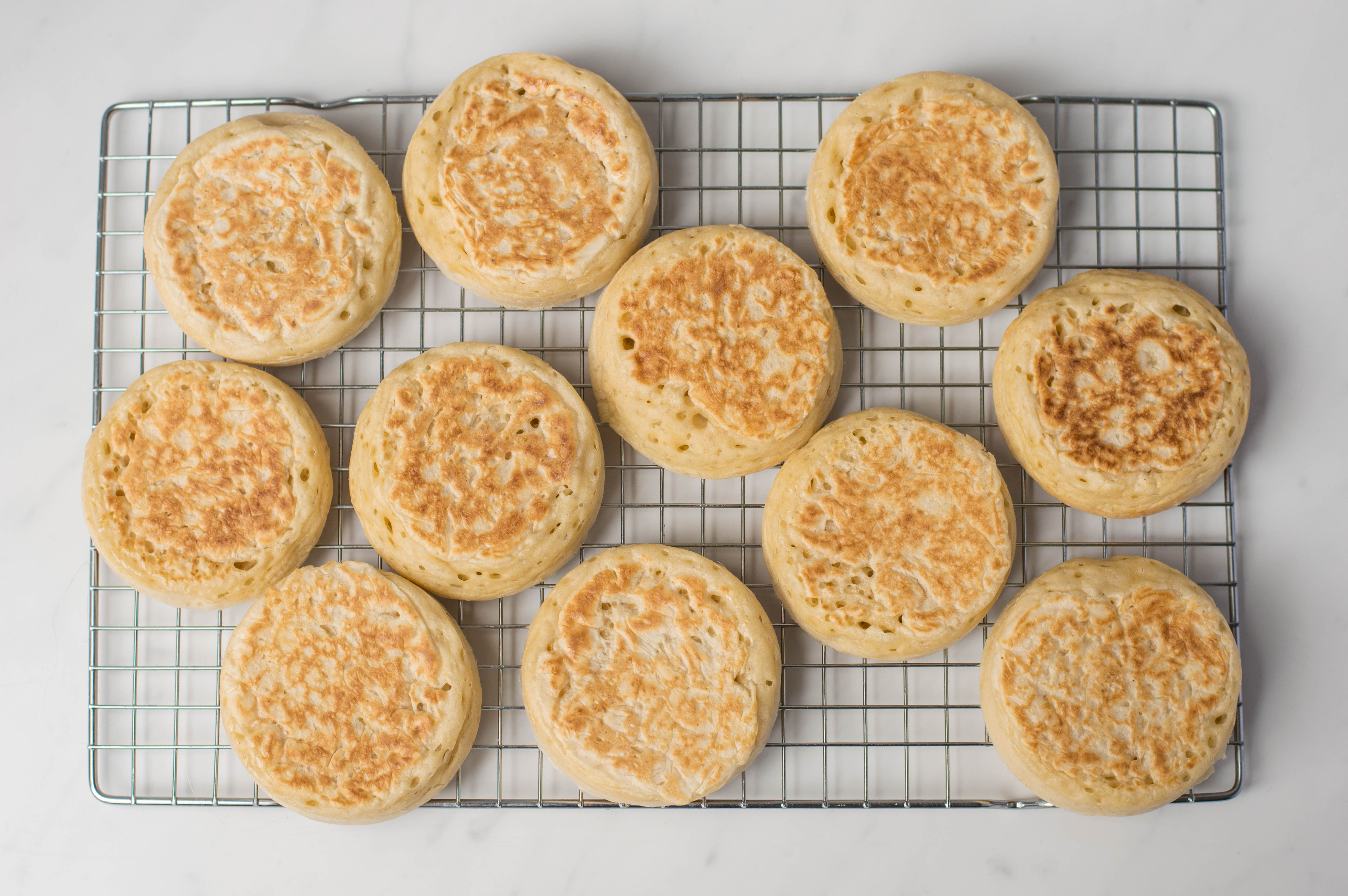 Crumpets cooking on a wire rack