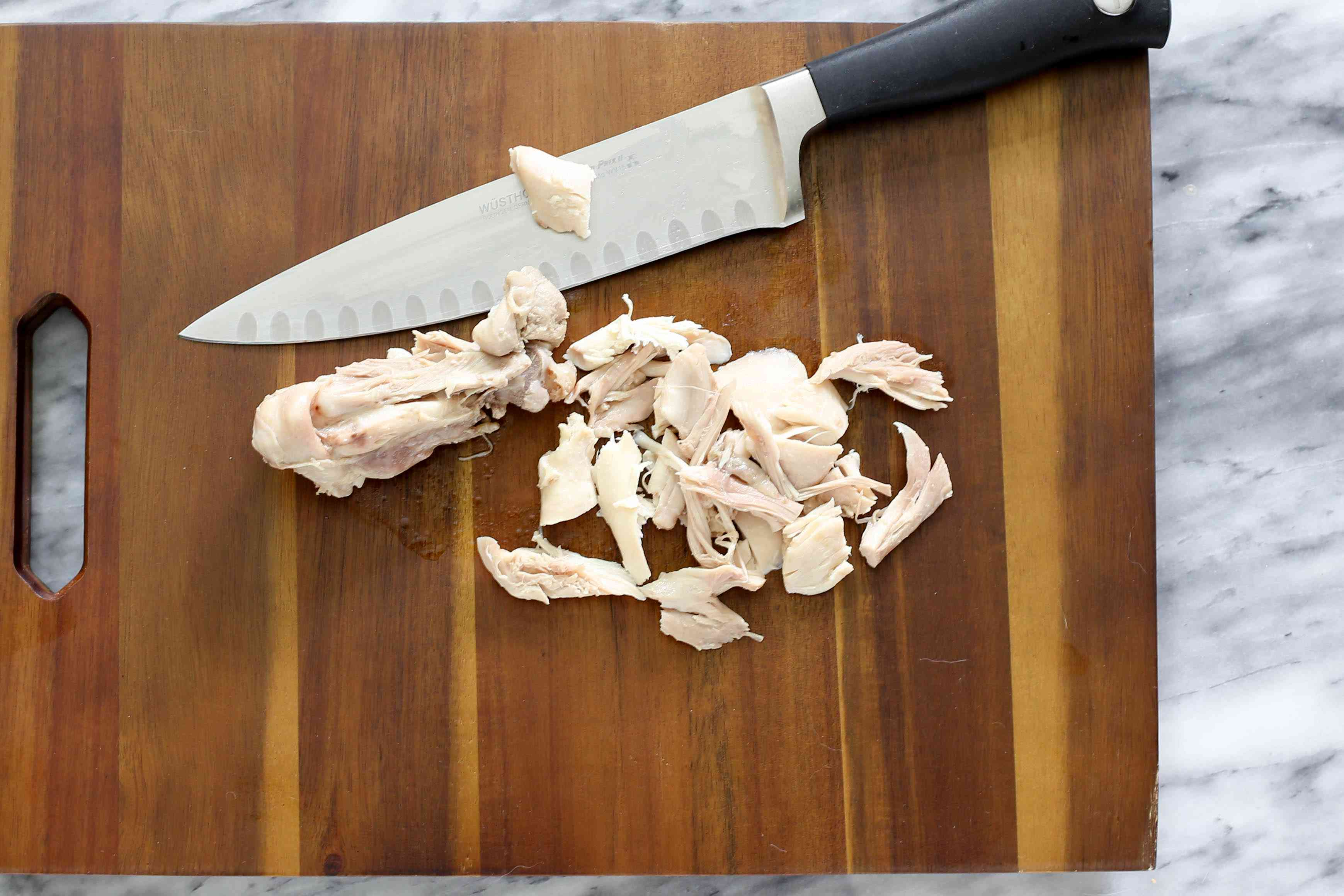Remove the chicken from the bones and chop.