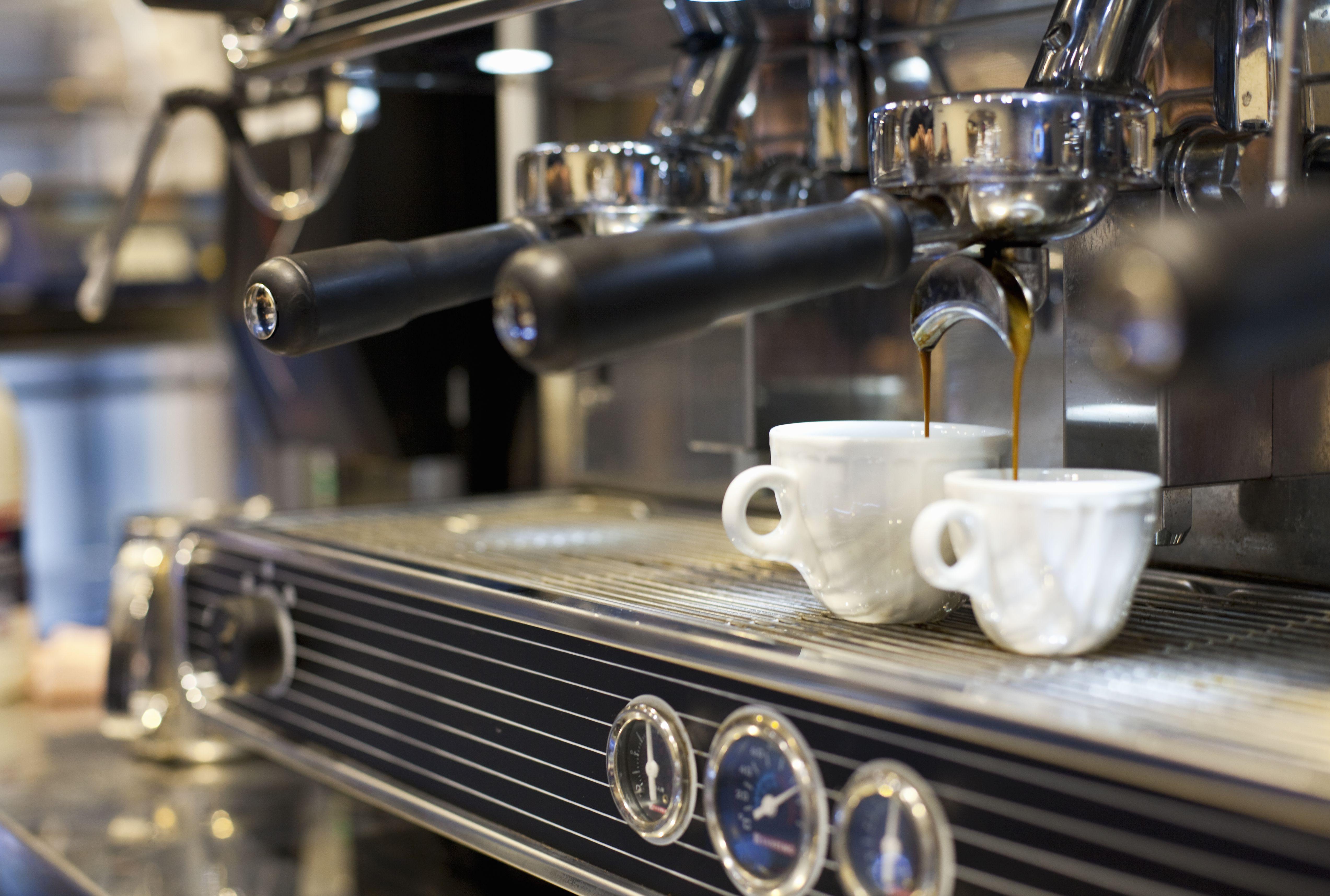 Espresso machine brewing coffee into cups