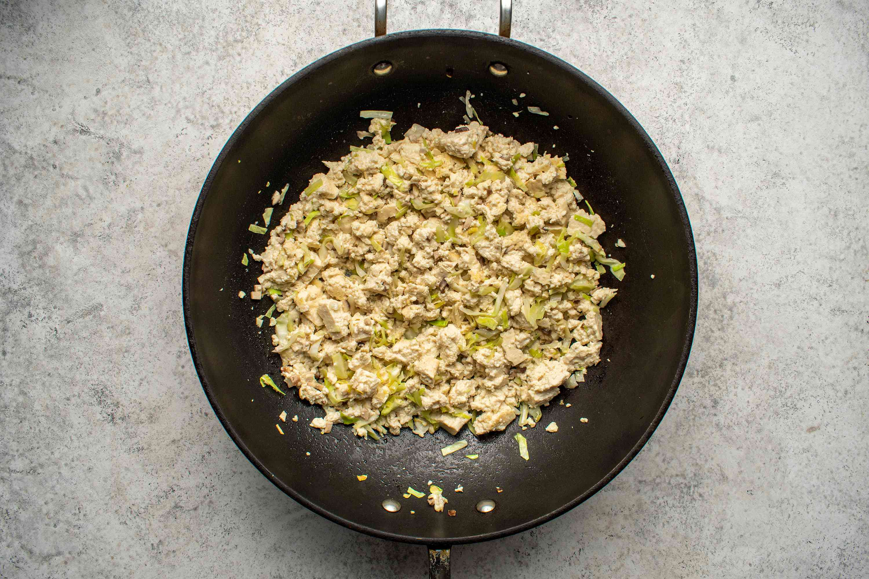 Saute the crumbled tofu, mushrooms, cabbage, ginger, and garlic in a wok