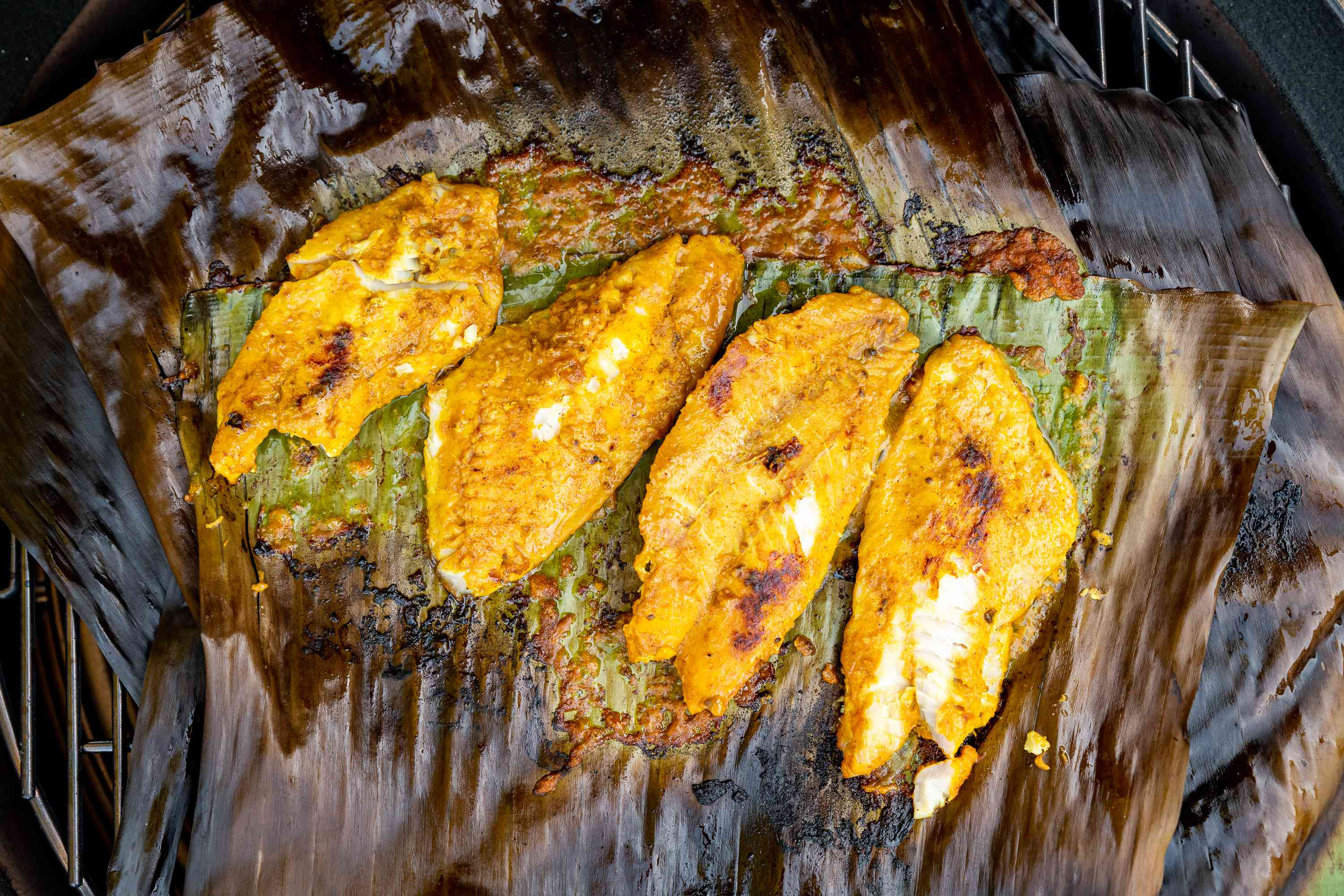 fish cooking on a banana leaves on a grill