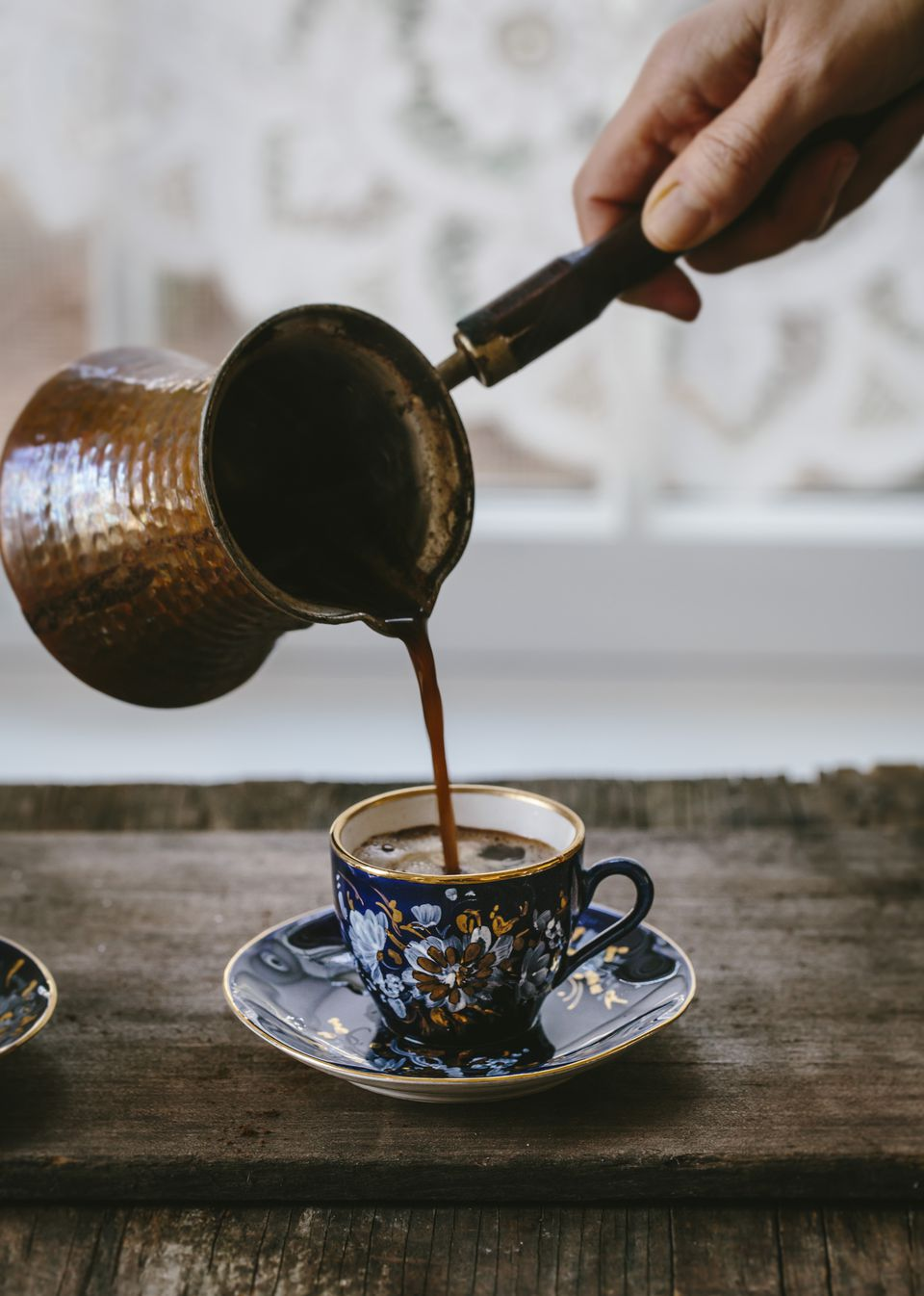A woman is pouring Turkish Coffee in to a vintage Turkish coffee cup.