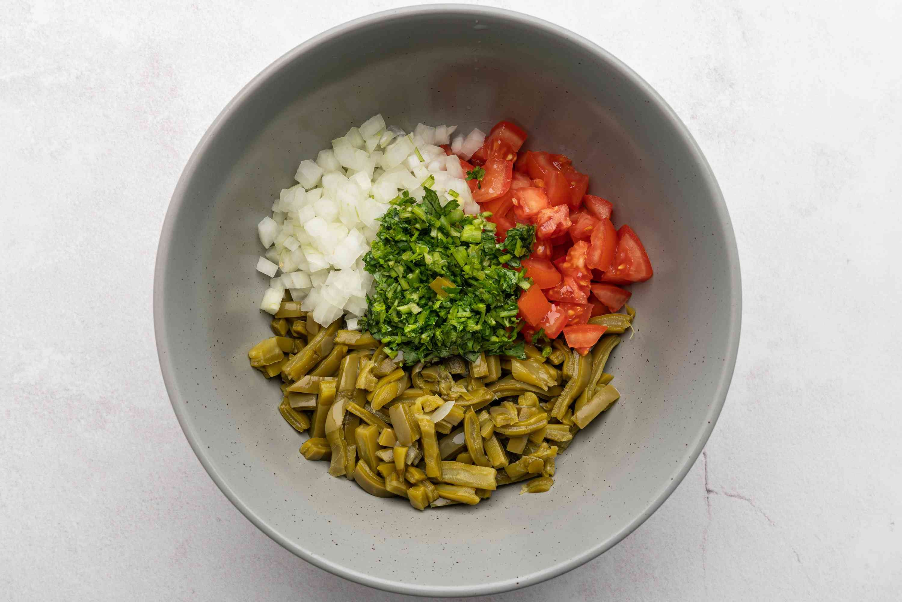 toss together tomato, onion, nopales, and cilantro in a bowl