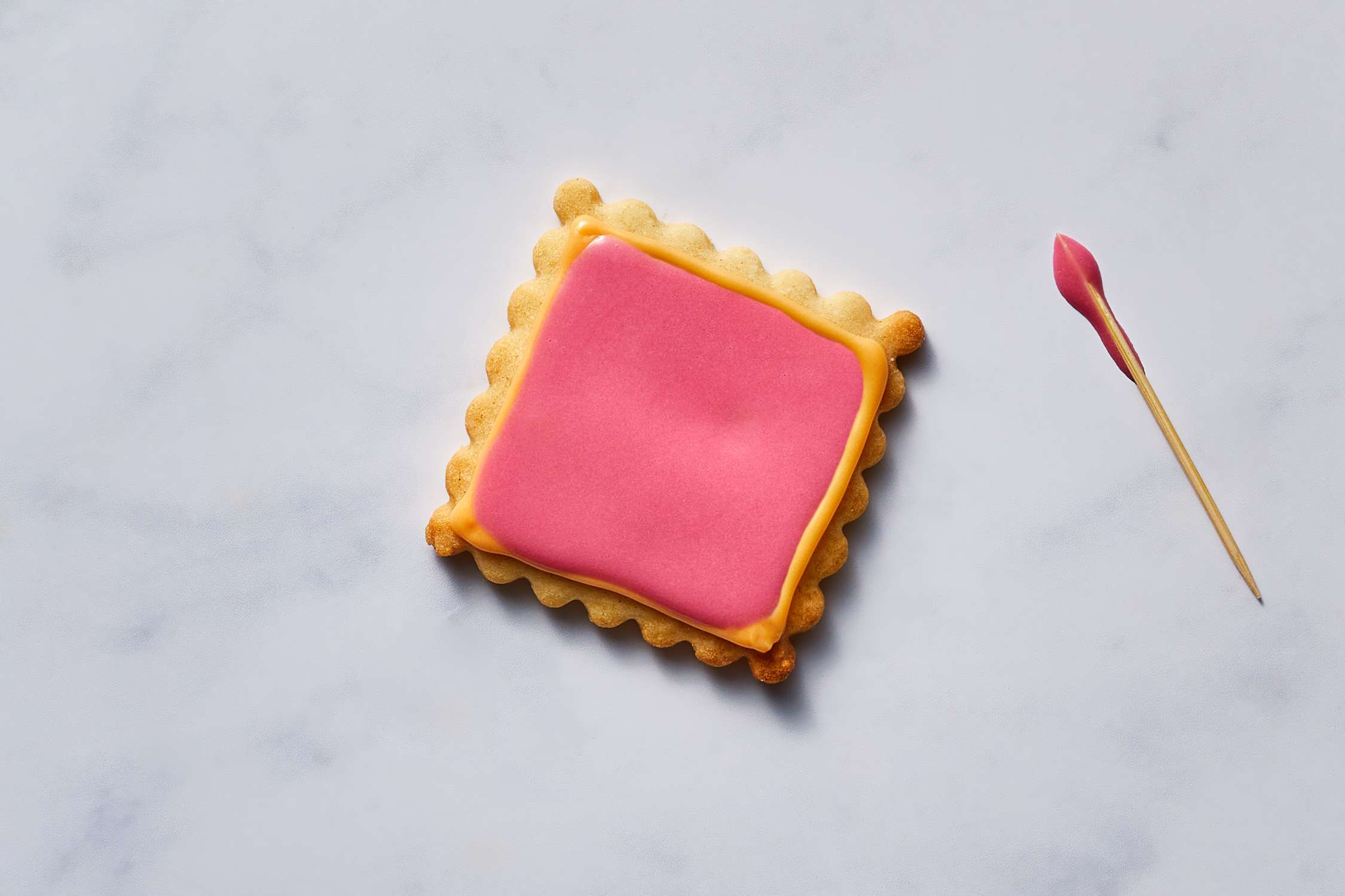 Toothpick to spreading the pink icing/frosting on cookie
