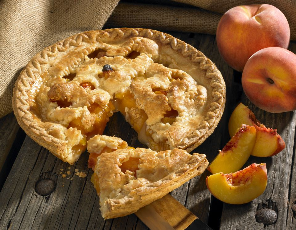 Peach pie on wood rustic background with peaches