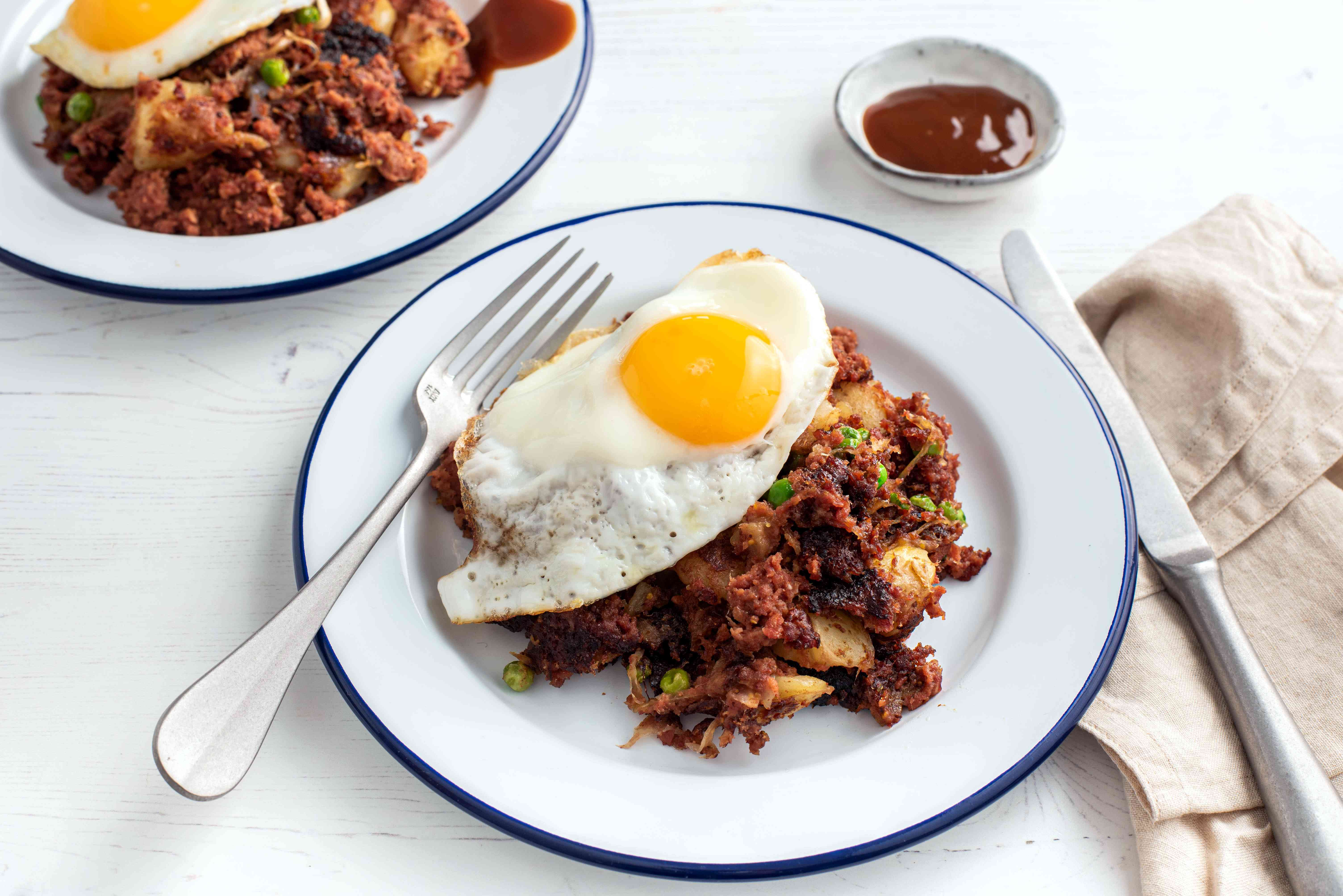 sunny side up egg on top of British Corned Beef Hash on a white plate