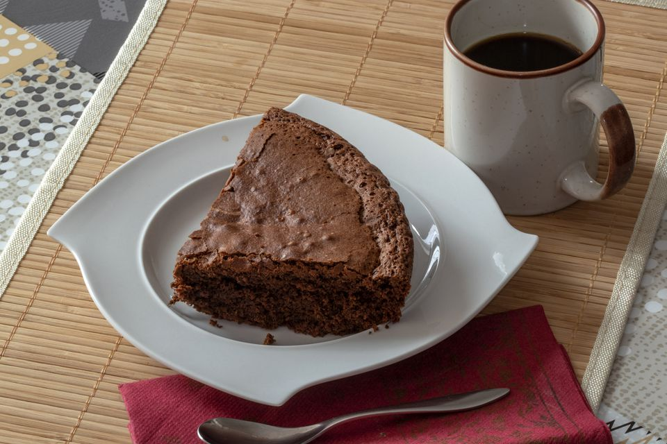 Chocolate cake on a plate with a mug of coffee