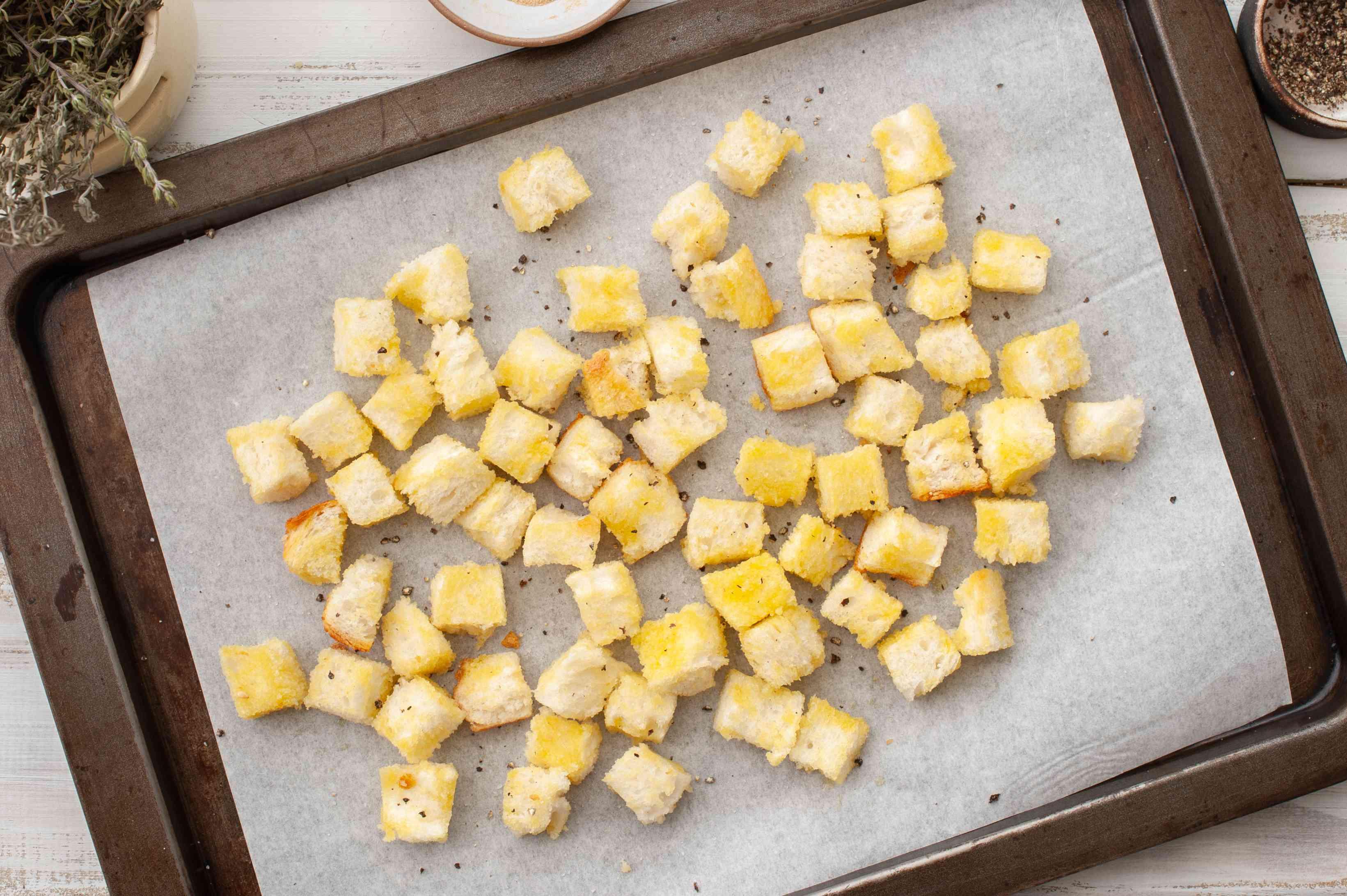 Seasoned bread cubes on a baking sheet