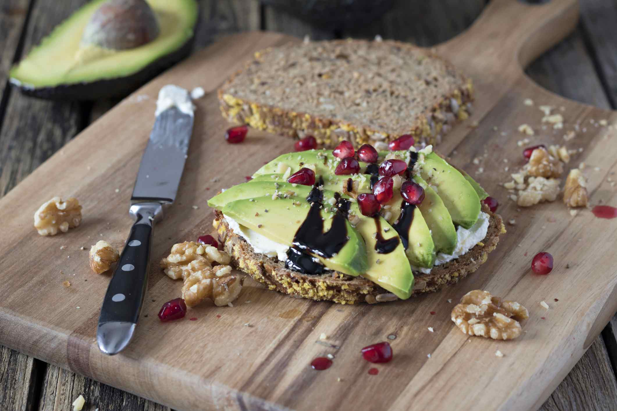 A sandwich board of avocado toast with pomegranate seeds
