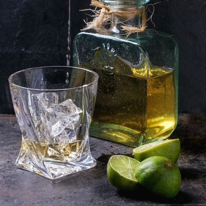Close-Up Of Tequila Pouring In Glass By Limes On Table
