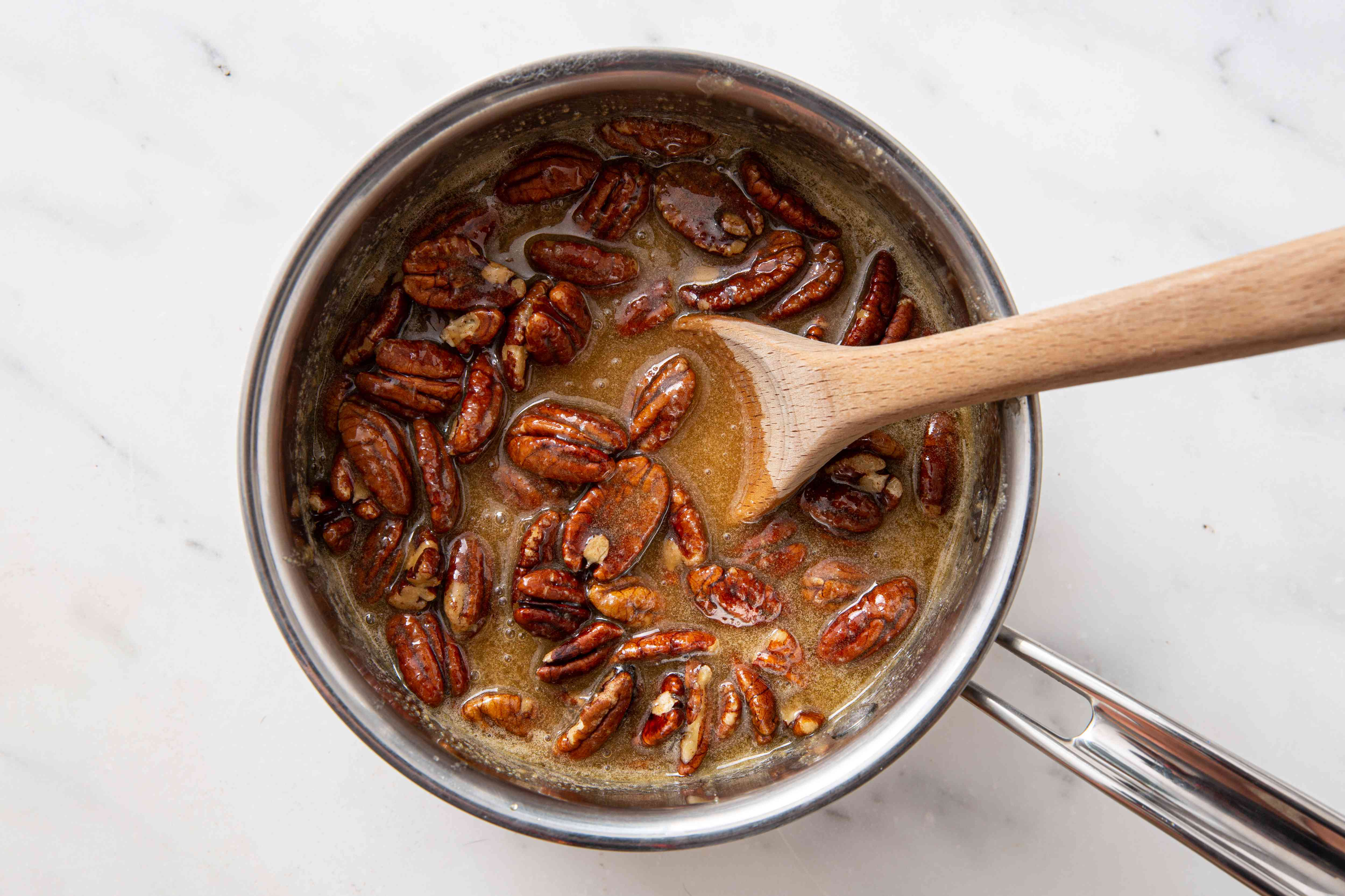 Whole pecans in the praline mixture in a saucepan